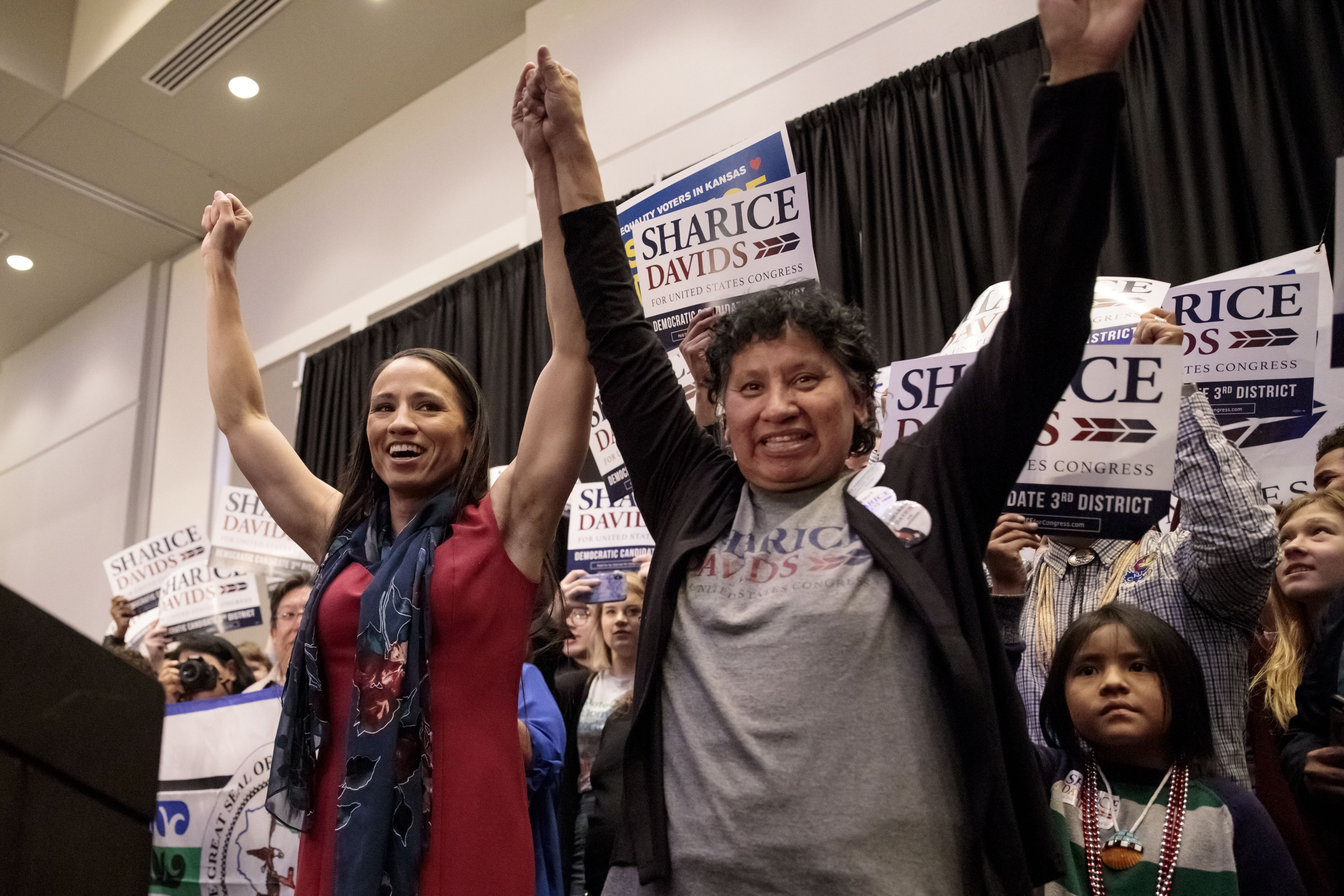 OLATHE, KS - NOVEMBER 06: Democratic candidate for Kansas' 3rd Congressional District Sharice Davids (L) and her mother, Crystal Herriage, celebrate with supporters during an election night party on November 6, 2018 in Olathe, Kansas. Davids defeated incumbent Republican Kevin Yoder. (Photo by Whitney Curtis/Getty Images)