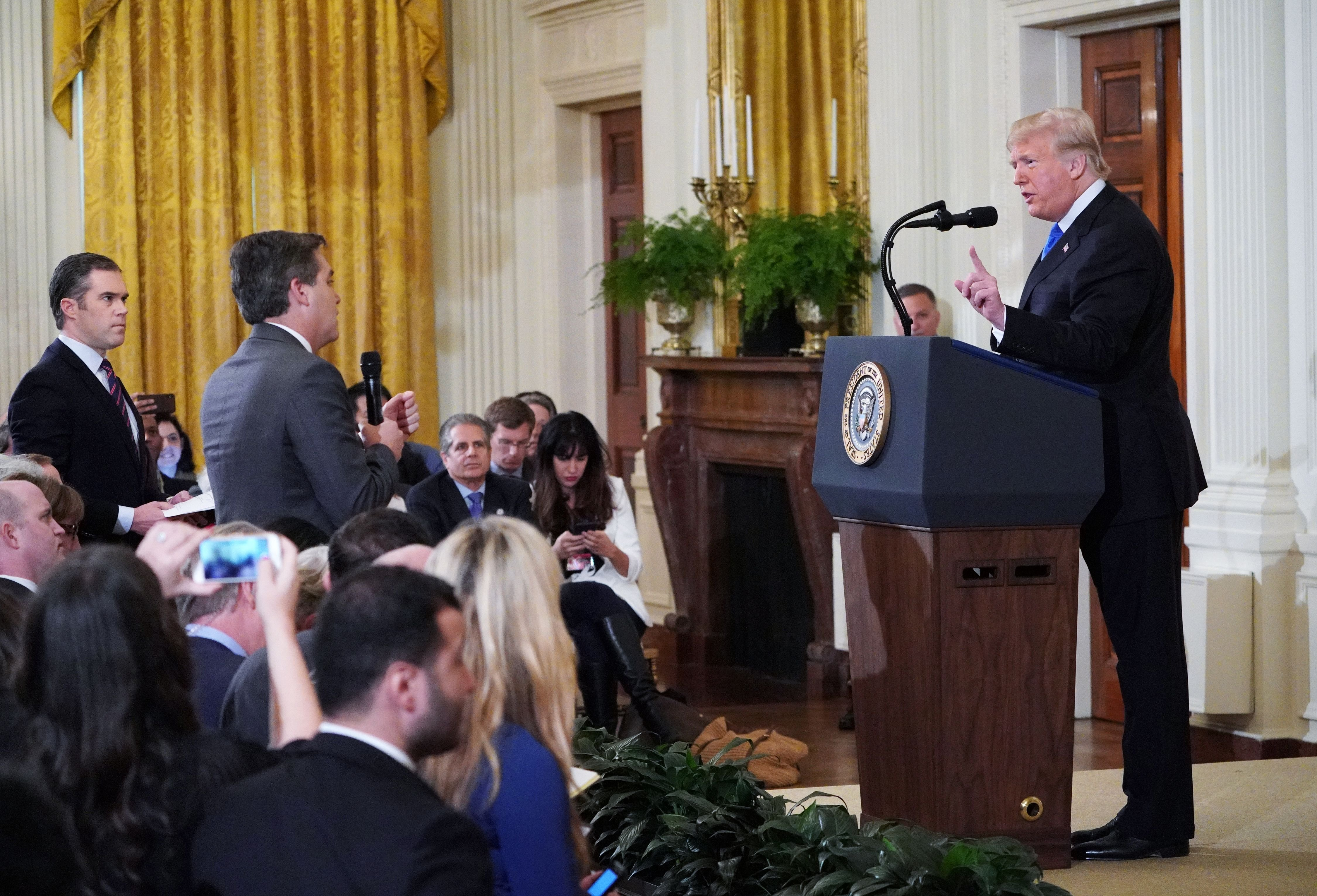 TOPSHOT - US President Donald Trump (R) gets into a heated exchange with CNN chief White House correspondent Jim Acosta (C) as NBC correspondent Peter Alexander (L) looks on during a post-election press conference in the East Room of the White House in Washington, DC on November 7, 2018. (Photo by MANDEL NGAN / AFP) (Photo credit should read MANDEL NGAN/AFP/Getty Images)