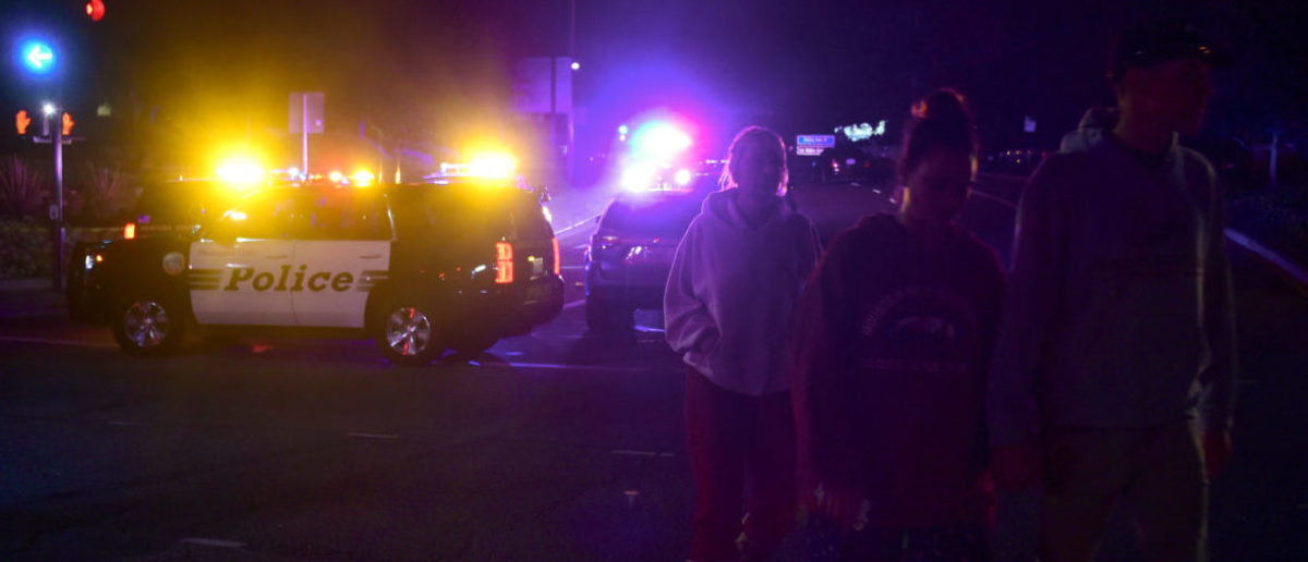 People walk away from the scene as it unfurls at the intersection of US 101 freeway and the Moorpark Rad exit as police vehicles close off the area responding to a shooting at a bar in Thousand Oaks, California on November 8, 2018. - Twelve people, including a police sergeant, were shot dead in a shooting at a night club close to Los Angeles, police said Thursday. All the victims were killed inside the bar in the suburb of Thousand Oaks late on Wednesday, including the officer who had been called to the scene, Sheriff Geoff Dean told reporters. The gunman was also dead at the scene, Dean added. The bar was hosting a college country music night. (Photo by Frederic J. BROWN / AFP)
