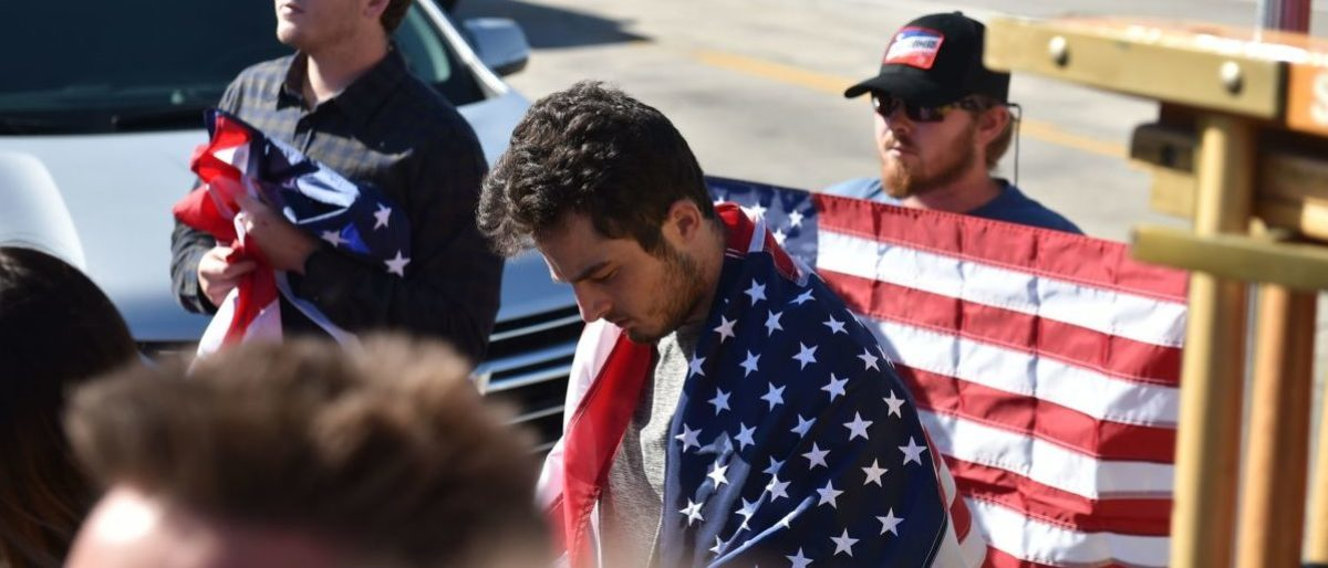 Men drape themselves in US flags as they watch a motorcade procession transporting the body of Sheriff's Sergeant Ron Helus, the first victim named in the mass shooting at a country bar in Thousand Oaks, California, November 8, 2018 - The gunman who killed 12, including Helus, people in a crowded California country music bar has been identified as 28-year-old Ian David Long, a former Marine, the local sheriff said Thursday. The suspect, who was armed with a .45-caliber handgun, was found deceased at the Borderline Bar and Grill, the scene of the shooting in the city of Thousand Oaks northwest of downtown Los Angeles. (Photo by Robyn Beck / AFP)