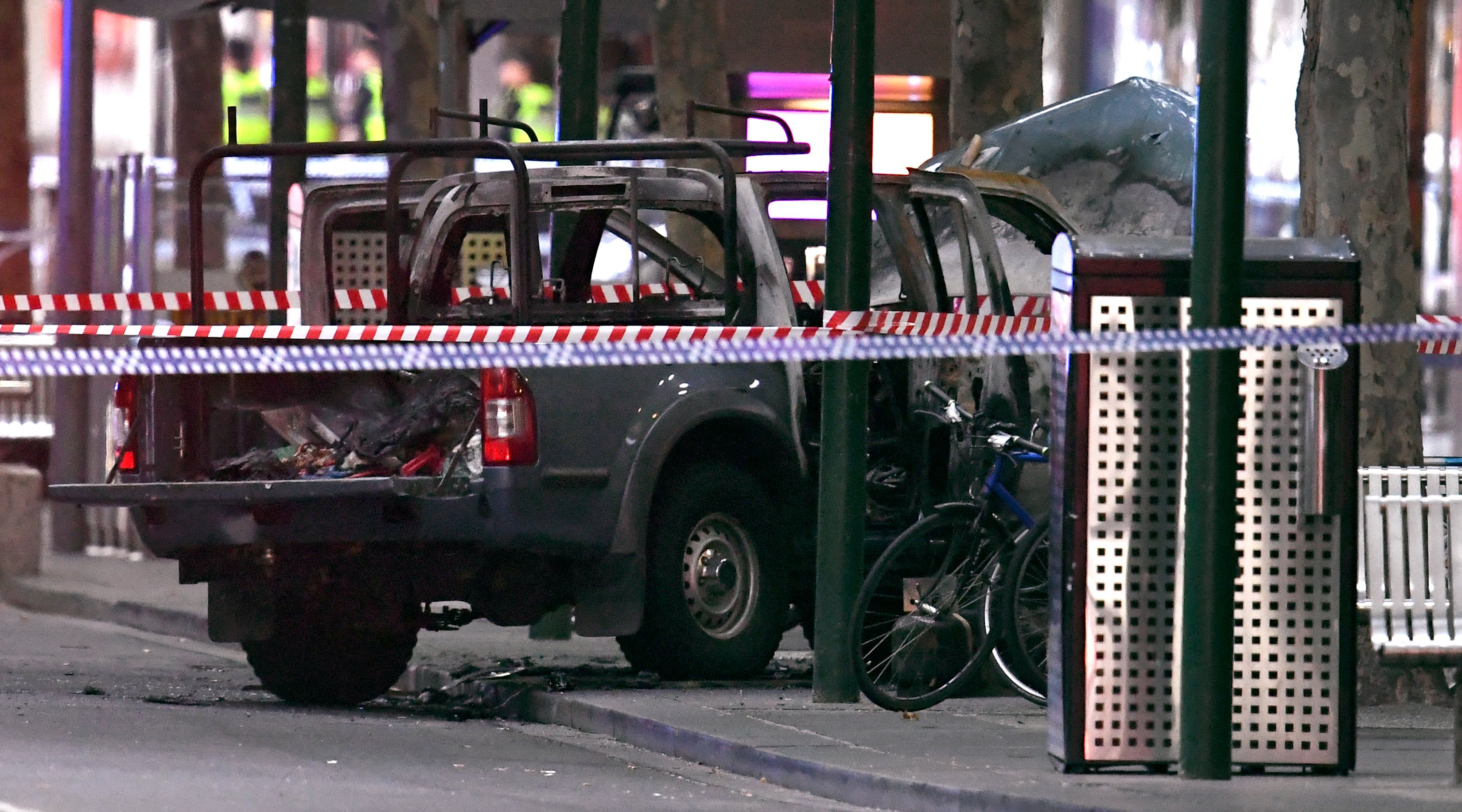 A burnt out vehicle is pictured at the crime scene following a stabbing incident in Melbourne on November 9, 2018. - One person was killed and two others injured in a rush hour stabbing incident in Melbourne's bustling central business district on November 9, prompting police to shoot a knife-wielding suspect near a burning vehicle. (Photo by William WEST / AFP)