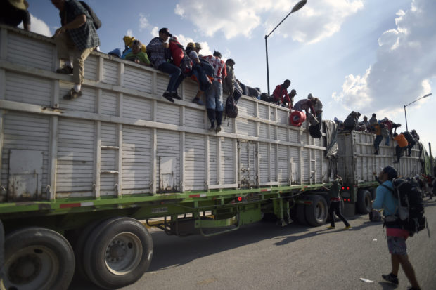 Central American migrants -mostly Hondurans- taking part in a caravan heading to the US, descend from a truck, on arrival at a temporary shelter in Irapuato, Guanajuato state, Mexico on November 11, 2018. - The trek from tropical Central America to the huge capital of Mexico is declining the health of the migrant caravan that endures extreme climate changes, as well as overcrowding and physical exhaustion, and still has to face the desert that leads to the United States. (Photo by ALFREDO ESTRELLA / AFP) (Photo credit should read ALFREDO ESTRELLA/AFP/Getty Images)