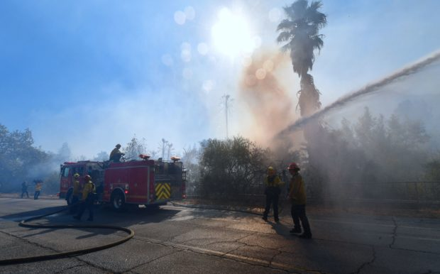 Water from a firetruck douses flames and smoke near homes in West Hills, California, on November 11, 2018, as firefighters continue their battle to control the Woolsey Fire. - Near Los Angeles, where the fire is threatening mansions and mobile homes alike in the coastal celebrity redoubt of Malibu, the death toll has so far been limited to two victims found in a vehicle on a private driveway. (Photo by Frederic J. BROWN / AFP) (Photo credit should read FREDERIC J. BROWN/AFP/Getty Images)