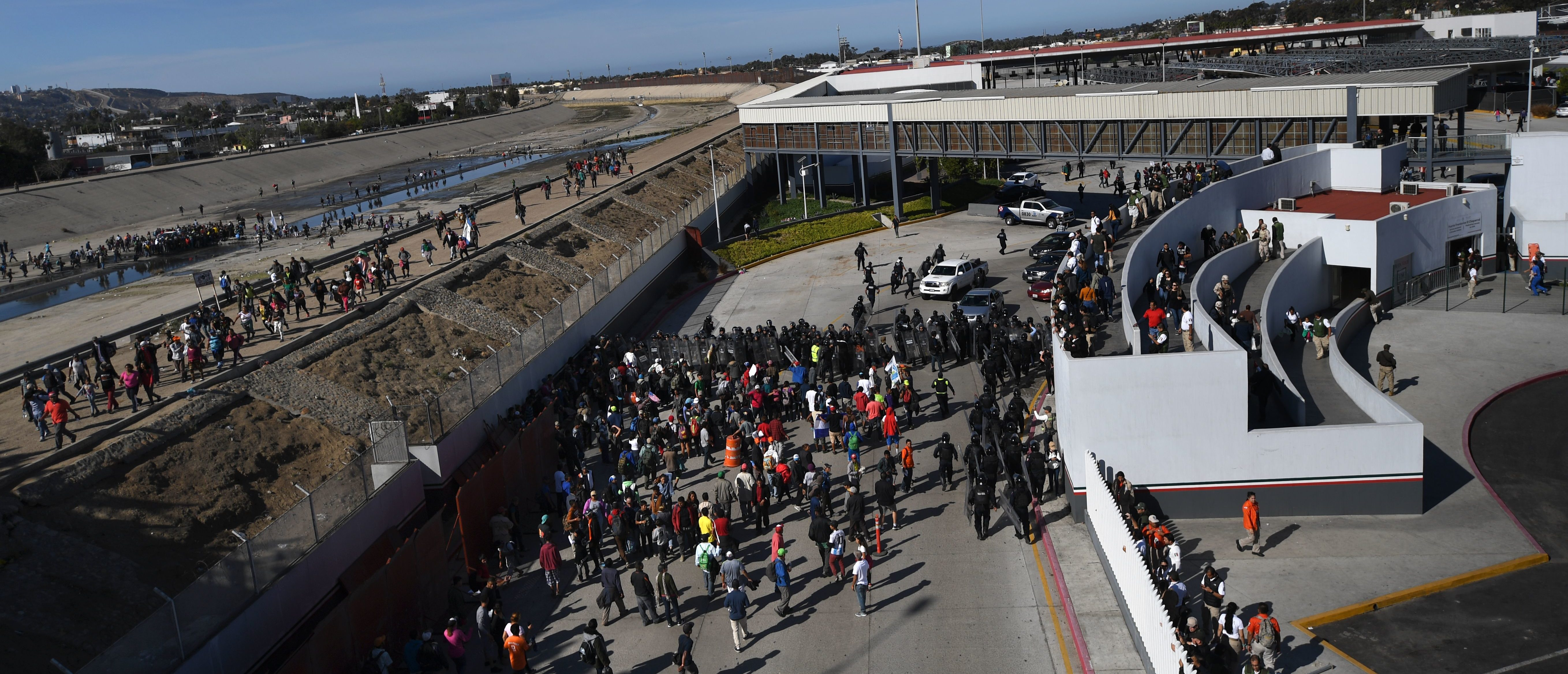 A group of Central American migrants -mostly from Honduras- get to El Chaparral port of entry after crossing the almost dry riverbed of the Tijuana River, in Tijuana, Baja California State, Mexico, on November 25, 2018. - Hundreds of migrants attempted to storm a border fence separating Mexico from the US on Sunday amid mounting fears they will be kept in Mexico while their applications for a asylum are processed. An AFP photographer said the migrants broke away from a peaceful march at a border bridge and tried to climb over a metal border barrier in the attempt to enter the United States. (Photo by Pedro PARDO / AFP)