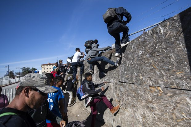 "A group of Central American migrants -mostly from Honduras- get over a fence as they try to reach the US-Mexico border near the El Chaparral border crossing in Tijuana, Baja California State, Mexico, on November 25, 2018. - US officials closed the San Ysidro crossing point in southern California on Sunday after hundreds of migrants, part of the ""caravan"" condemned by President Donald Trump, tried to breach a fence from Tijuana, authorities announced. (Photo by Pedro PARDO / AFP) (Photo credit should read PEDRO PARDO/AFP/Getty Images)"