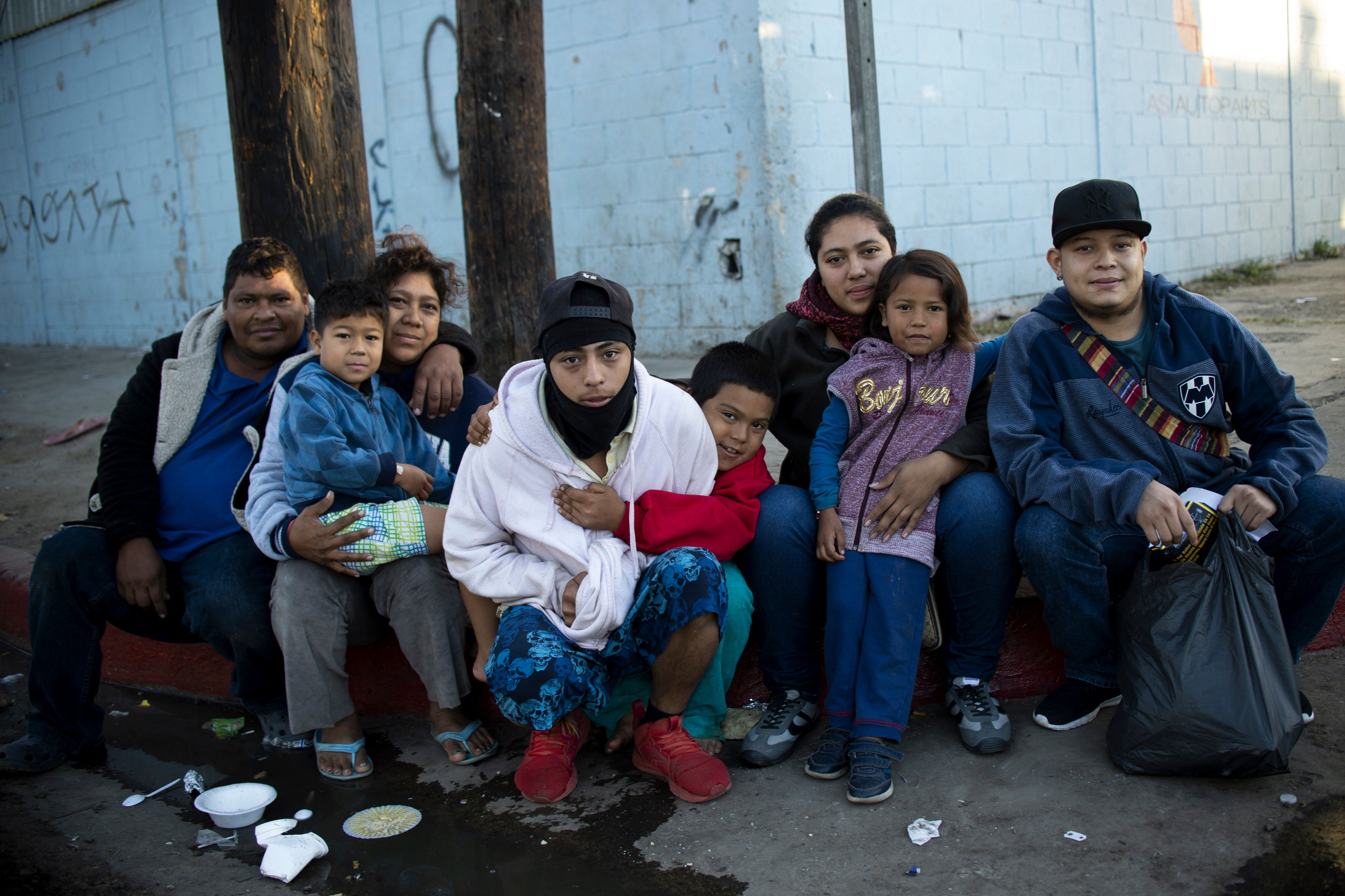 A family from Honduras pose for picture outside a temporary shelter in Tijuana, Baja California State, Mexico, near the US-Mexico border on November 26, 2018. (Photo by PEDRO PARDO / AFP)