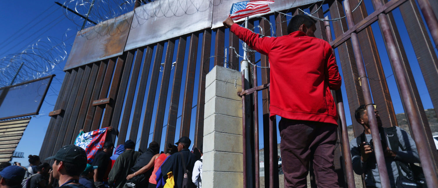 TIJUANA, MEXICO - NOVEMBER 25: Junior, a migrant from Honduras, waves the American flag while standing with other migrants at the U.S.-Mexico border fence on November 25, 2018 in Tijuana, Mexico. Migrants made their way to the location along the border after evading a police blockade as they attempted to approach the El Chaparral port of entry. U.S. Customs and Border Protection temporarily closed two ports of entry on the border with Tijuana in response. Around 6,000 migrants from Central America have arrived in the city with the mayor of Tijuana declaring the situation a 'humanitarian crisis'. (Photo by Mario Tama/Getty Images)