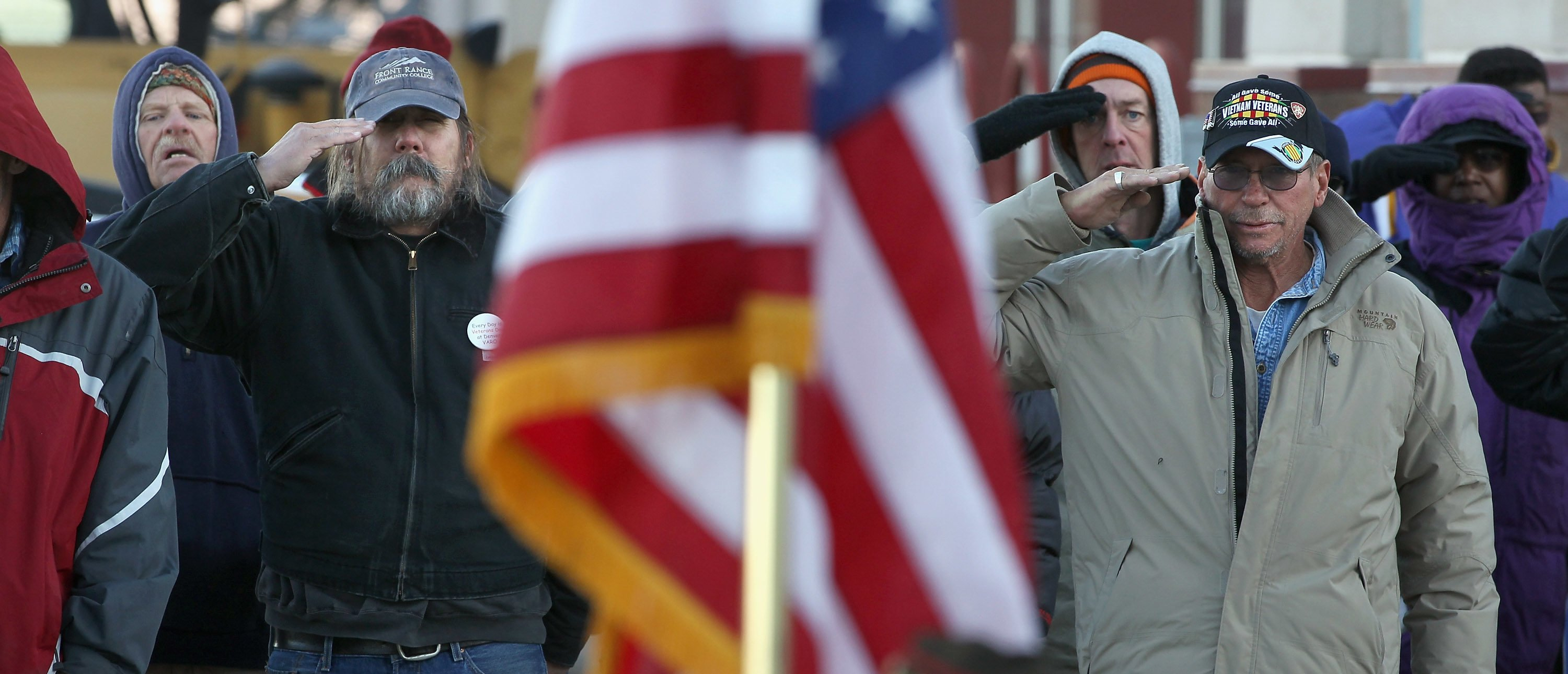 "DENVER, CO - NOVEMBER 03: Homeless U.S. military veterans salute the flag during the Pledge of Allegiance at a ""Stand Down"" event hosted by the Department of Veterans Affairs on November 3, 2011 in Denver, Colorado. A week ahead of Veterans Day, more than 500 homeless veterans were expected to attend the event, where they received free clothing, medical care, employment assistance and were able to see a judge to resolve legal issues. Organizers say the homeless veterans population has surged in recent years with the high national unemployment rate. Stand Down is a military term that means a temporary stop of offensive military action. (Photo by John Moore/Getty Images)"