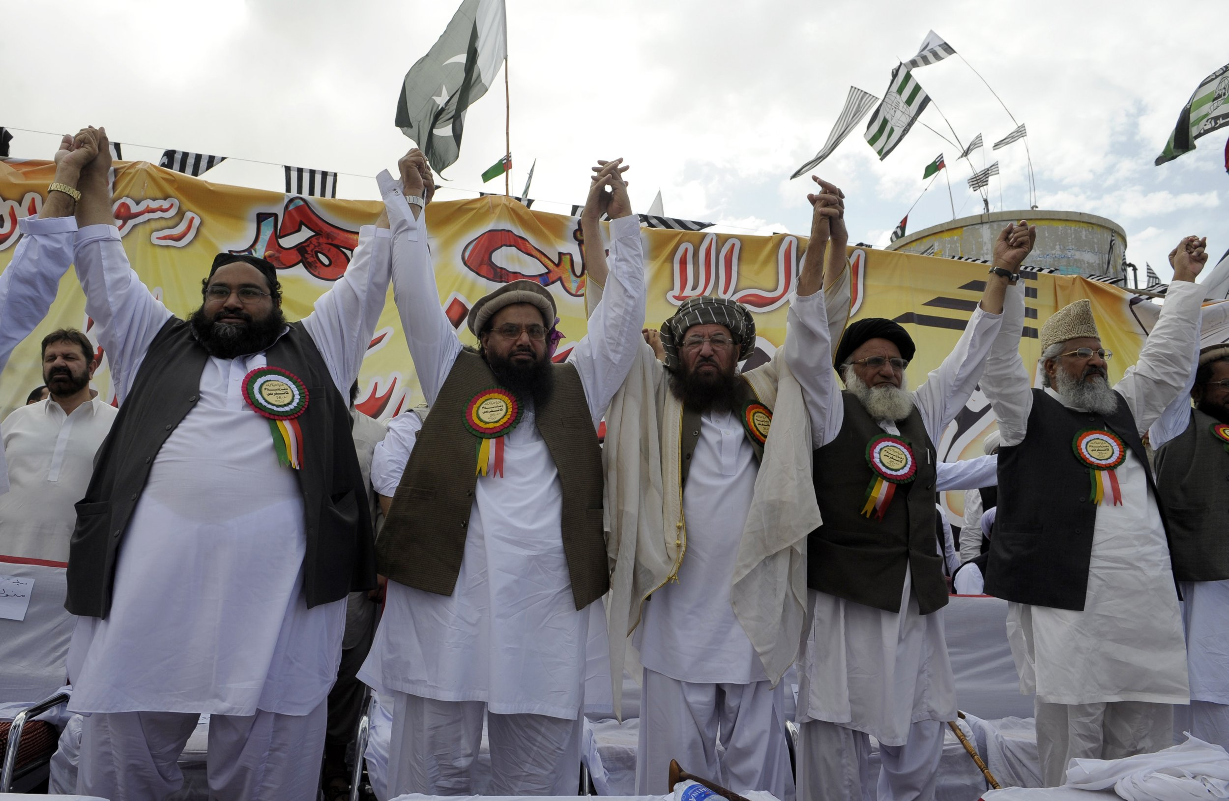 Hafiz Saeed (2nd L), the founder of Lashkar-e-Taiba, and Maulana Samiul Haq (C), chief of the Defence Council of Pakistan join hands with other leaders during an anti-US rally in Quetta on April 26, 2012, against the reopening of the NATO supply route to Afghanistan. Islamabad on April 26 reiterated its opposition to US drone attacks in its territory as Washington's point man on Pakistan and Afghanistan arrived amid efforts to mend fractured relations. Relations between Pakistan and the United States plunged last year over the US raid that killed Osama bin Laden inside Pakistan and a NATO air strike near the border with Afghanistan that killed 24 Pakistani soldiers. AFP PHOTO/BANARAS KHAN