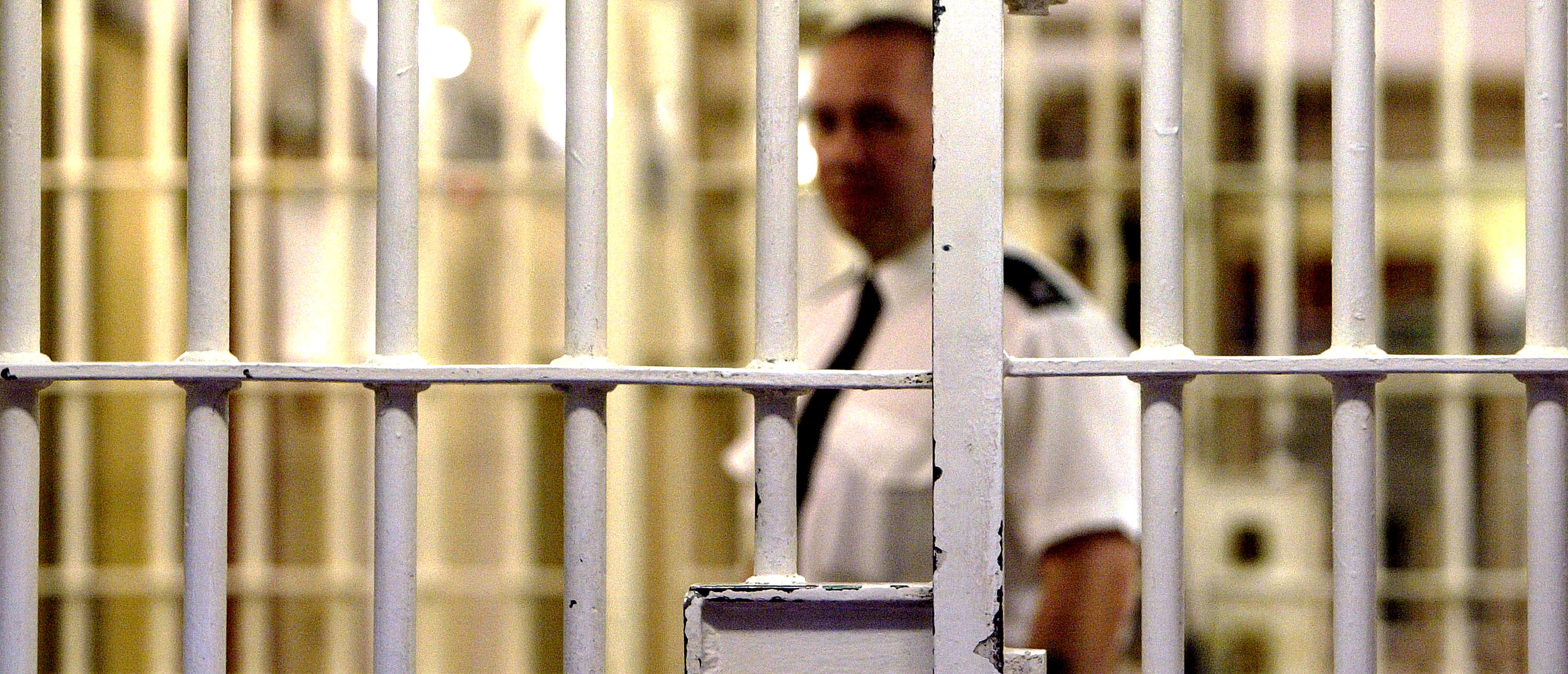 LONDON - MAY 19: (FILE PHOTO) A prison guard at HMP (Her Majesty's Prison) Pentonville stands behind a locked gate May 19, 2003 in London. A new report from the Prison Reform Trust (PRT) says overcrowding in Britain's prisons has been caused by tougher sentencing rather than an increase in crime. Since 1991, offenders of petty crimes are three times more likely to be imprisoned. (Photo by Ian Waldie/Getty Images)