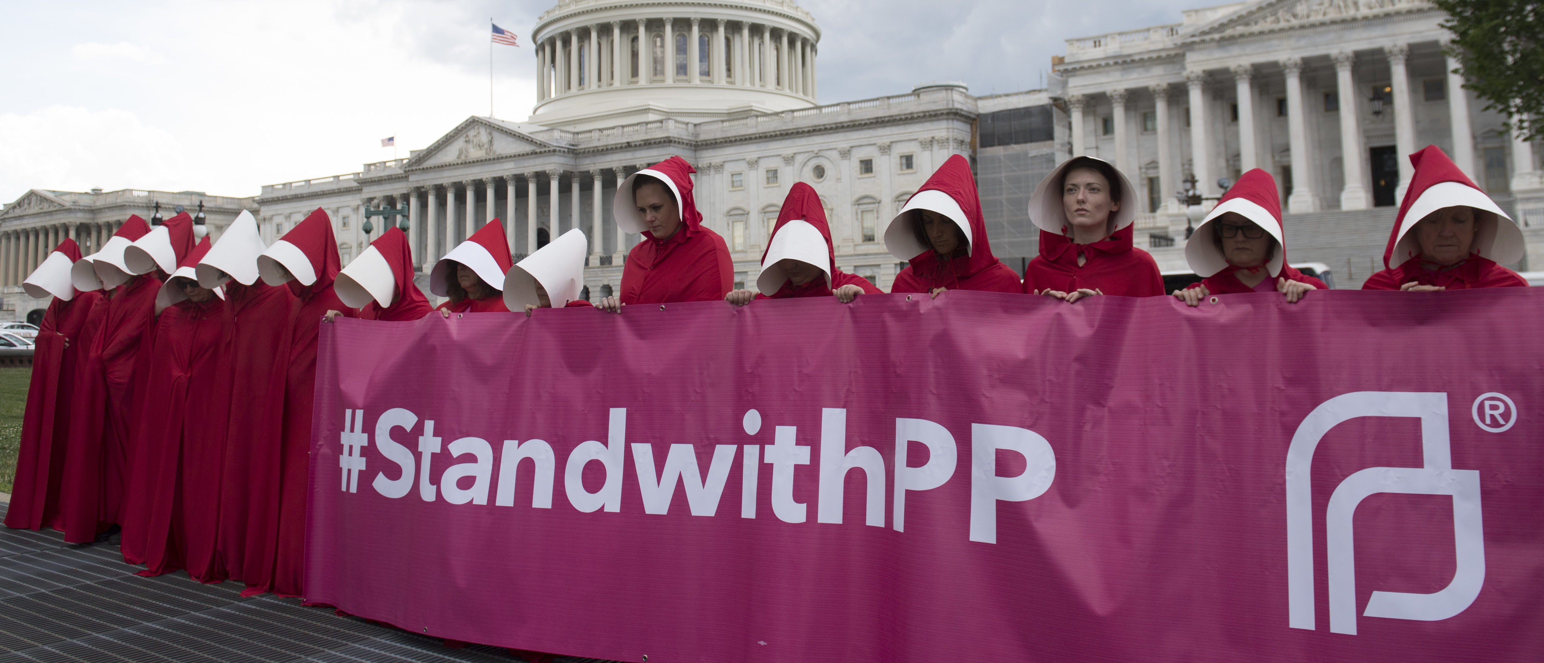 "Supporters of Planned Parenthood dressed as characters from ""The Handmaid's Tale,"" hold a rally as they protest the US Senate Republicans' healthcare bill outside the US Capitol in Washington, DC, June 27, 2017. / AFP PHOTO / SAUL LOEB (Photo credit should read SAUL LOEB/AFP/Getty Images)"