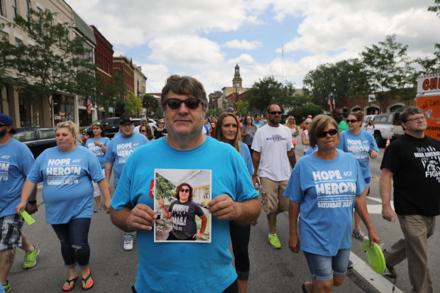 Barry Bova holds a picture of his son Brad, who died of a heroin overdose, while marching through the streets of Norwalk against the epidemic of heroin on July 14, 2017 in Norwalk, Ohio. Spencer Platt/Getty Images