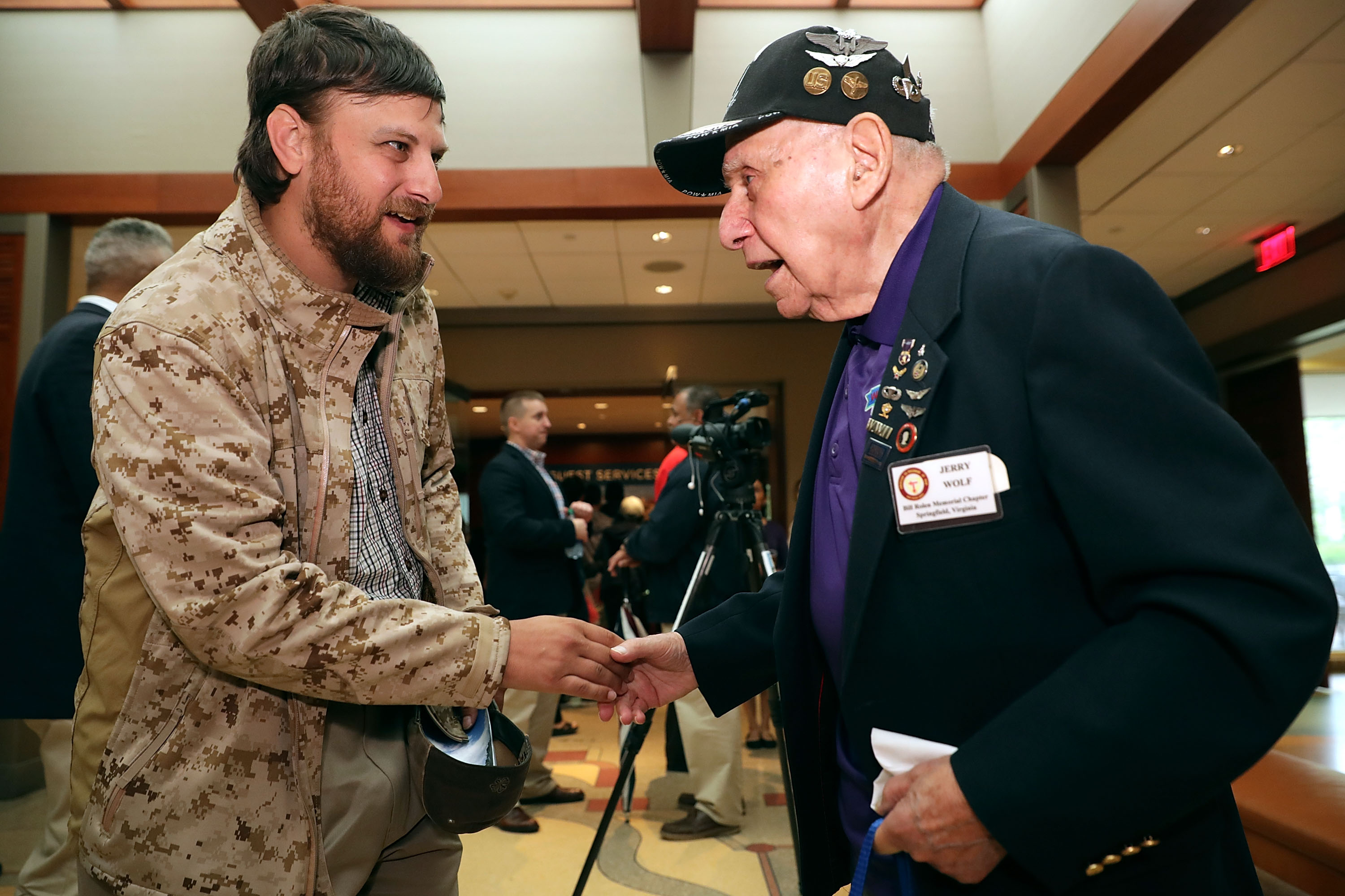 Iraq War veteran Derrick Anthony (L) of Quad Cities, IA, greets fellow Purple Heart recipient and WWII veteran and POW Jerry Wolf of during the National Purple Heart Day Ceremony at George Washington's Mount Vernon August 7, 2017 in Mount Vernon, Virginia. Chip Somodevilla/Getty Images