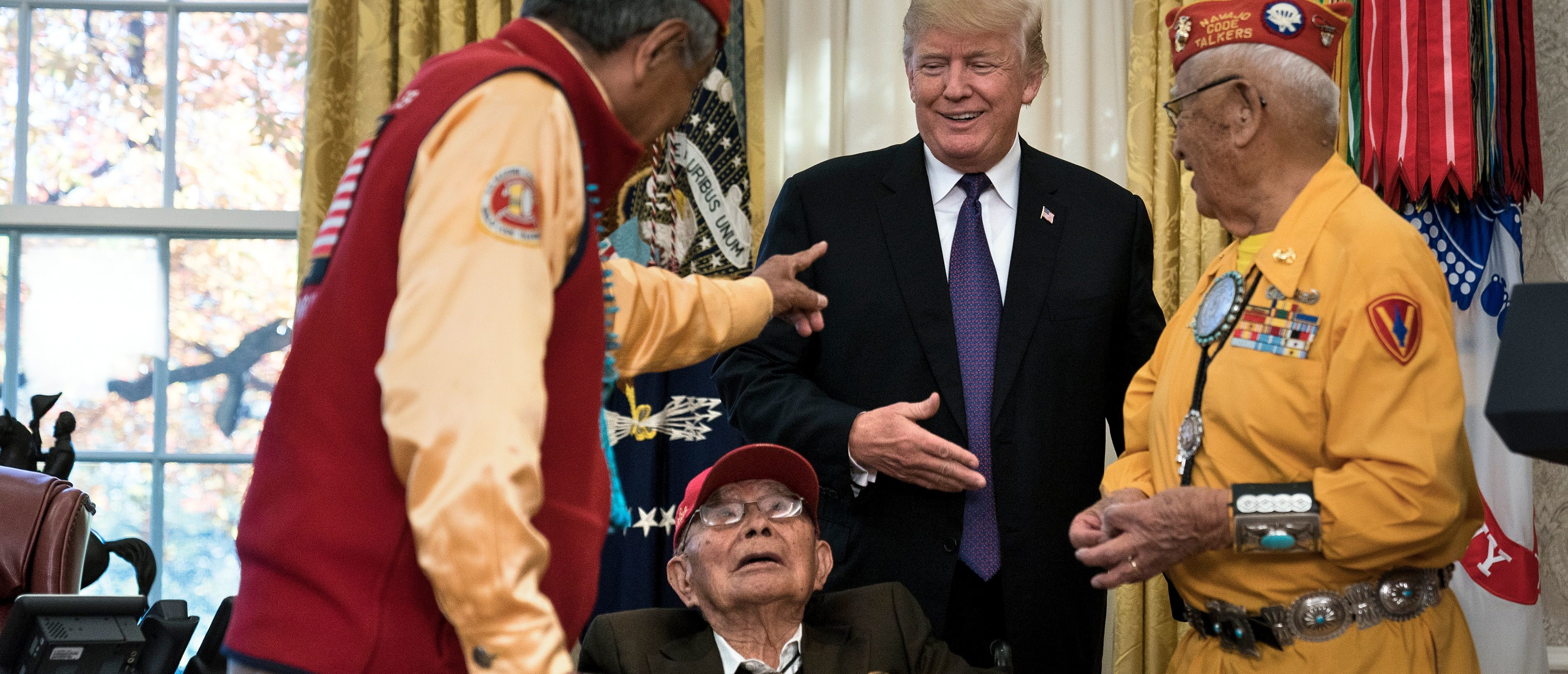 US President Donald Trump greets Navajo veterans in the Oval Office of the White House during an event honoring Native American code talkers who served in World War II on November 27, 2017 in Washington, DC. / AFP PHOTO / Brendan Smialowski (Photo credit should read BRENDAN SMIALOWSKI/AFP/Getty Images)