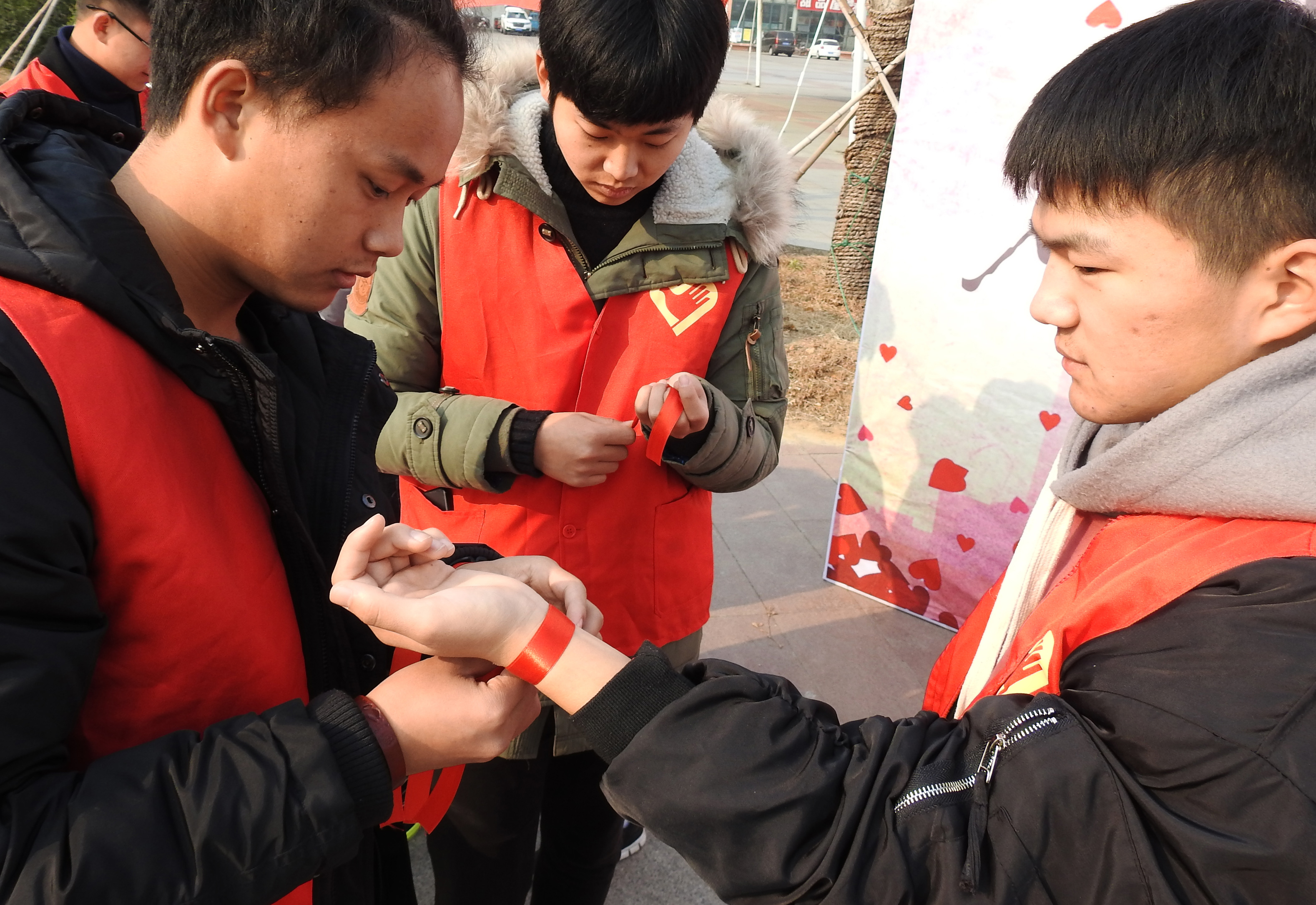 A university student ties a red ribbon on another's wrist to mark World AIDS Day in Lianyungang in China's eastern Jiangsu province on December 1, 2017. AFP/Getty Images