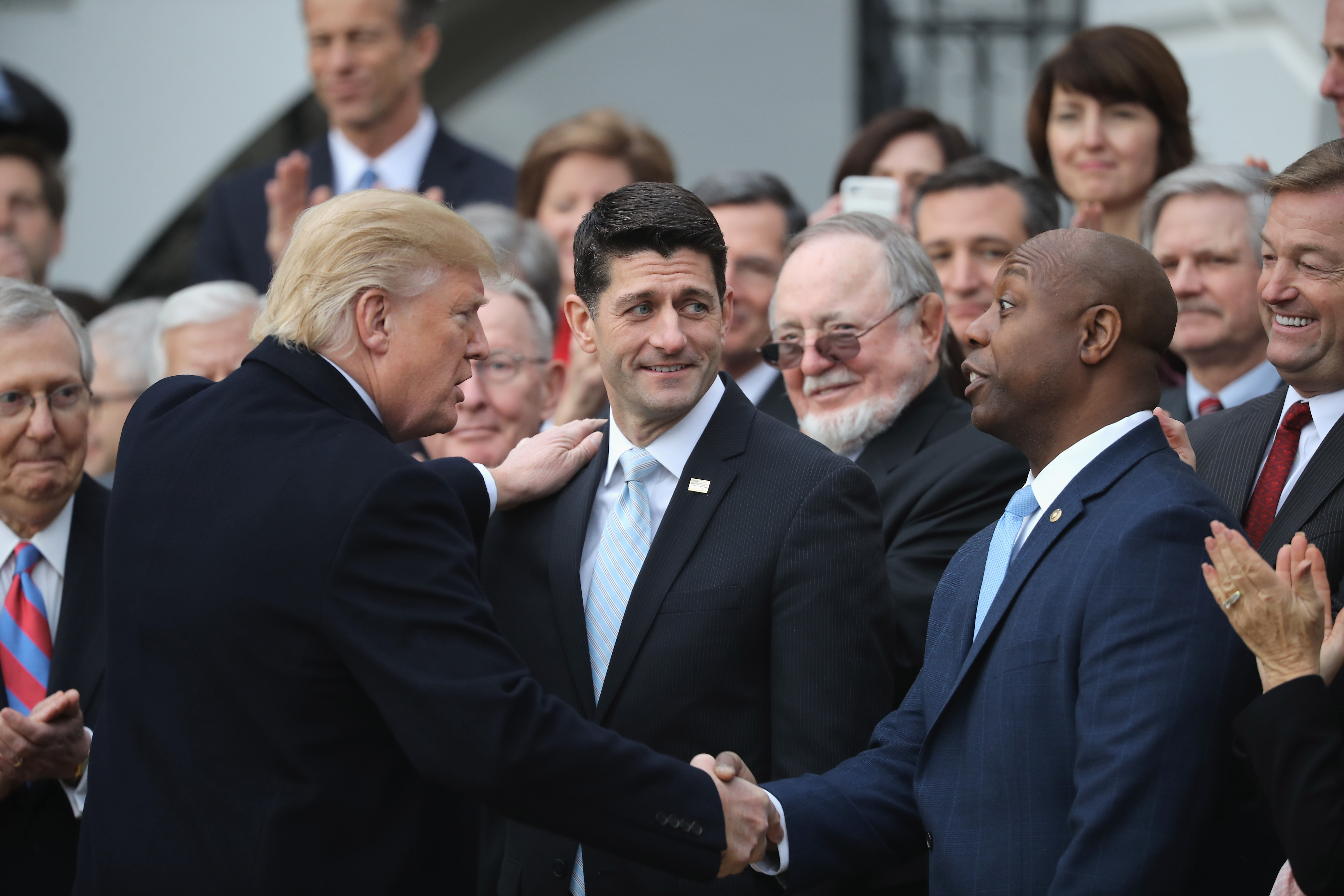 U.S. President Donald Trump congratulates Speaker of the House Paul Ryan (C) and Sen. Tim Scott at an event celebrating Congress passing the Tax Cuts and Jobs Act with Republican members of the House and Senate on the South Lawn of the White House on December 20, 2017 in Washington, DC. Chip Somodevilla/Getty Images
