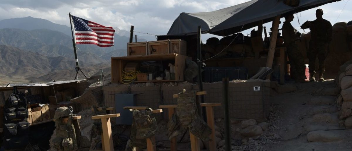"""In this photo taken on July 7, 2018, US Army soldiers from NATO looks on as U.S. flag flies in a checkpoint during a patrol against Islamic State militants at the Deh Bala district in the eastern province of Nangarhar Province. - A US soldier was killed and two others wounded in an """"apparent insider attack"""" in southern Afghanistan on July 8, NATO said, the first such killing in nearly a year. (Photo by WAKIL KOHSAR / AFP)"""