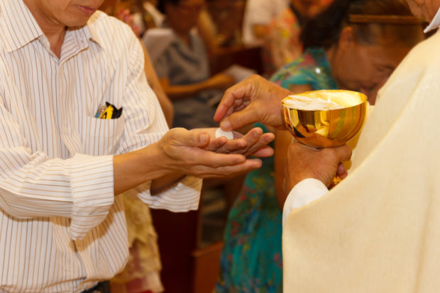 A Catholic priest dispenses the consecrated host used in the rite of Holy Communion (Shutterstock/Cavee)