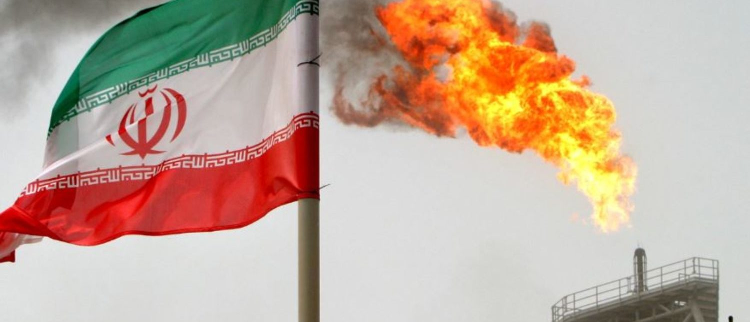 FILE PHOTO: A gas flare on an oil production platform in the Soroush oil fields is seen alongside an Iranian flag in the Persian Gulf, Iran, July 25, 2005./File Photo
