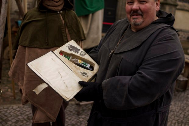 WITTENBERG, GERMANY - OCTOBER 31: A participant holds a bottle with alcohol in a book in the day to commemorate the 500th anniversary of Luther's nailing of his 95 theses on the doors of the nearby Schlosskirche church on October 31, 2017 in Wittenberg, Germany. (Photo by Carsten Koall/Getty Images)