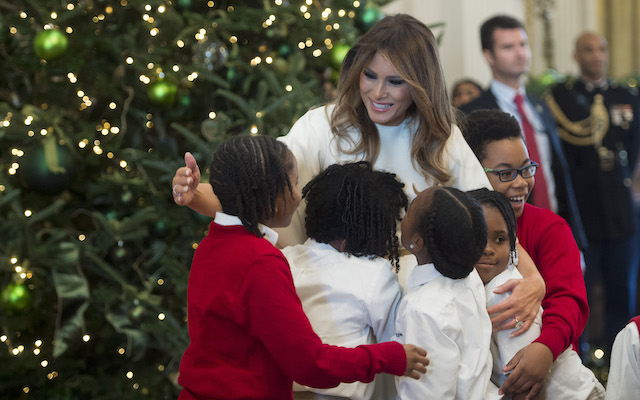 US First Lady Melania Trump hugs children in the East Room as she tours Christmas decorations at the White House in Washington, DC, November 27, 2017. (Photo credit: SAUL LOEB/AFP/Getty Images)