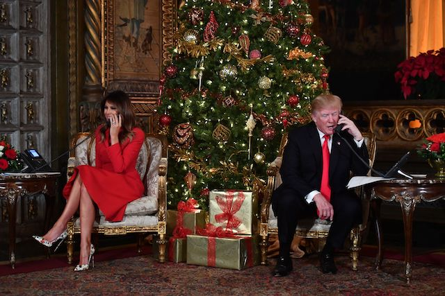 TOPSHOT - US President Donald J. Trump and the First Lady Melania Trump participate in NORAD Santa Tracker phone calls at the Mar-a-Lago resort in Palm Beach, Florida on December 24, 2017. (Photo credit: NICHOLAS KAMM/AFP/Getty Images)