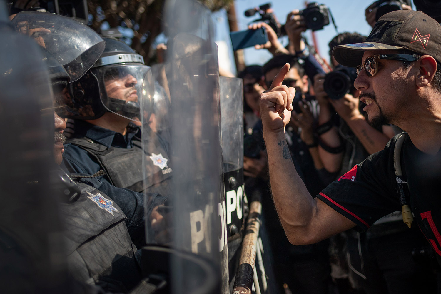 A demonstrator, part of a protest march against migrants, shouts towards a line of police in riot gear who were standing guard over a temporary shelter housing a caravan from Central America trying to reach the U.S., in Tijuana, Mexico November 18, 2018. REUTERS/Adrees Latif