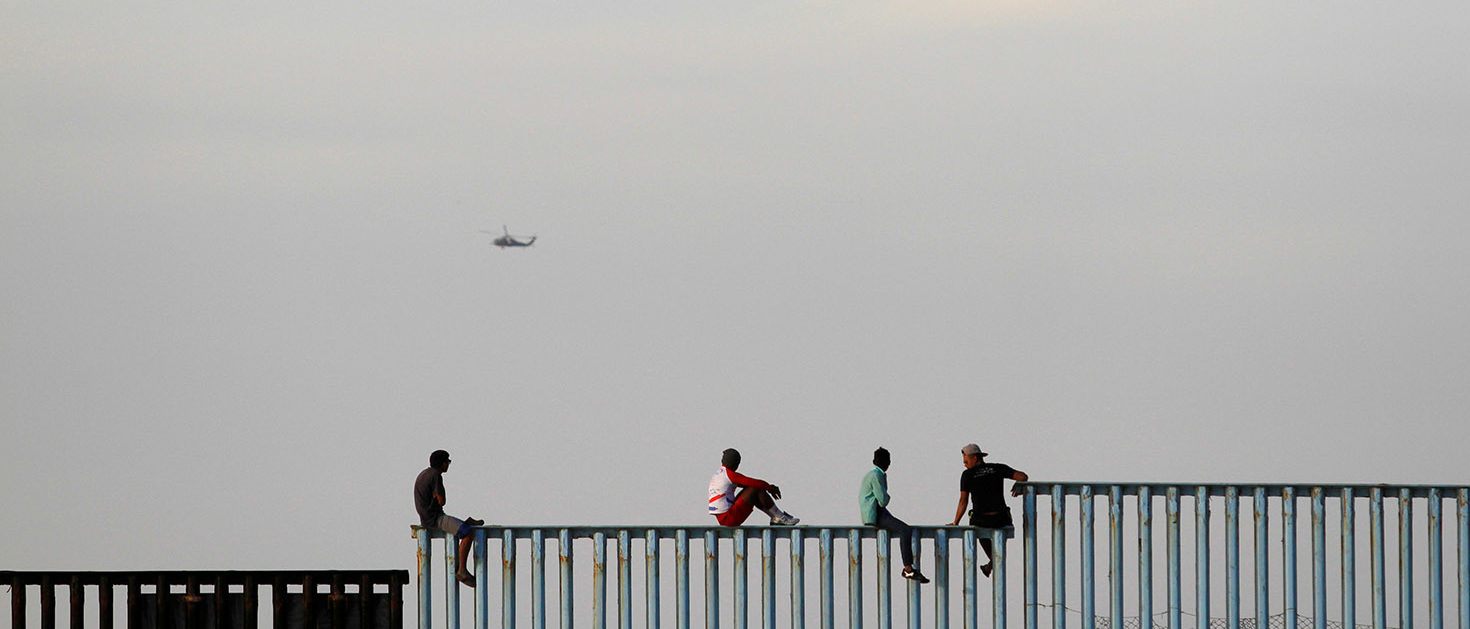Migrants, part of a caravan of thousands trying to reach the U.S., sit on top of the border fence between Mexico and the United States, after arriving in Tijuana, Mexico November 13, 2018. REUTERS/Jorge Duenes