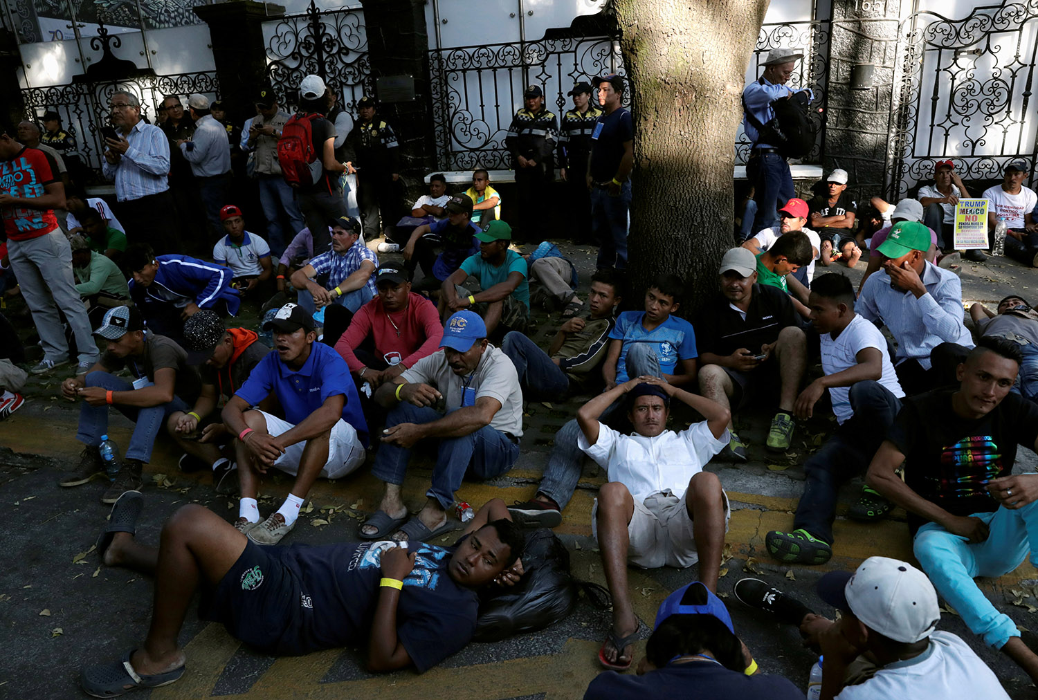 Migrants, part of a caravan traveling from Central America en route to the United States, wait outside a UN Refugee Agency (UNHCR) office during a march demanding buses to take them to the U.S. border, in Mexico City, Mexico November 8, 2018. REUTERS/Henry Romero/File Photo - RC185564C660
