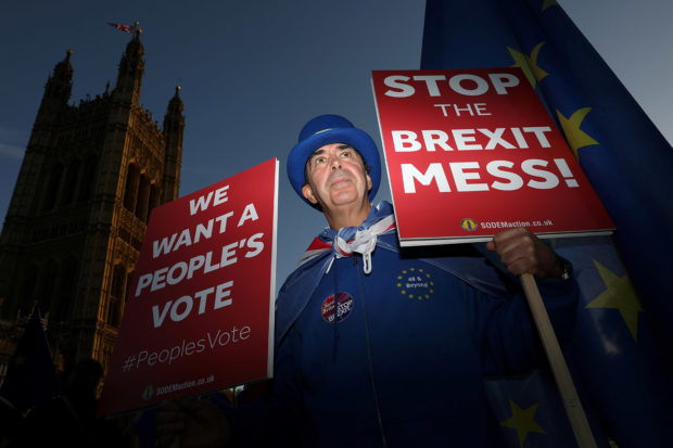 An anti-Brexit demonstrator hold placards opposite the Houses of Parliament, in London, Britain, November 13, 2018. REUTERS/Simon Dawson