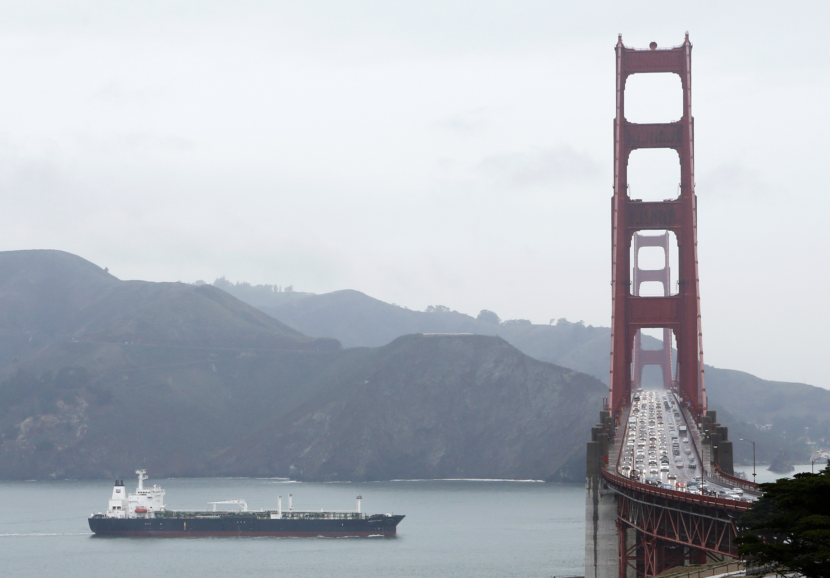 An oil tanker passes underneath the Golden Gate Bridge during a rainfall in San Francisco, California, February 26, 2014. REUTERS/Beck Diefenbach