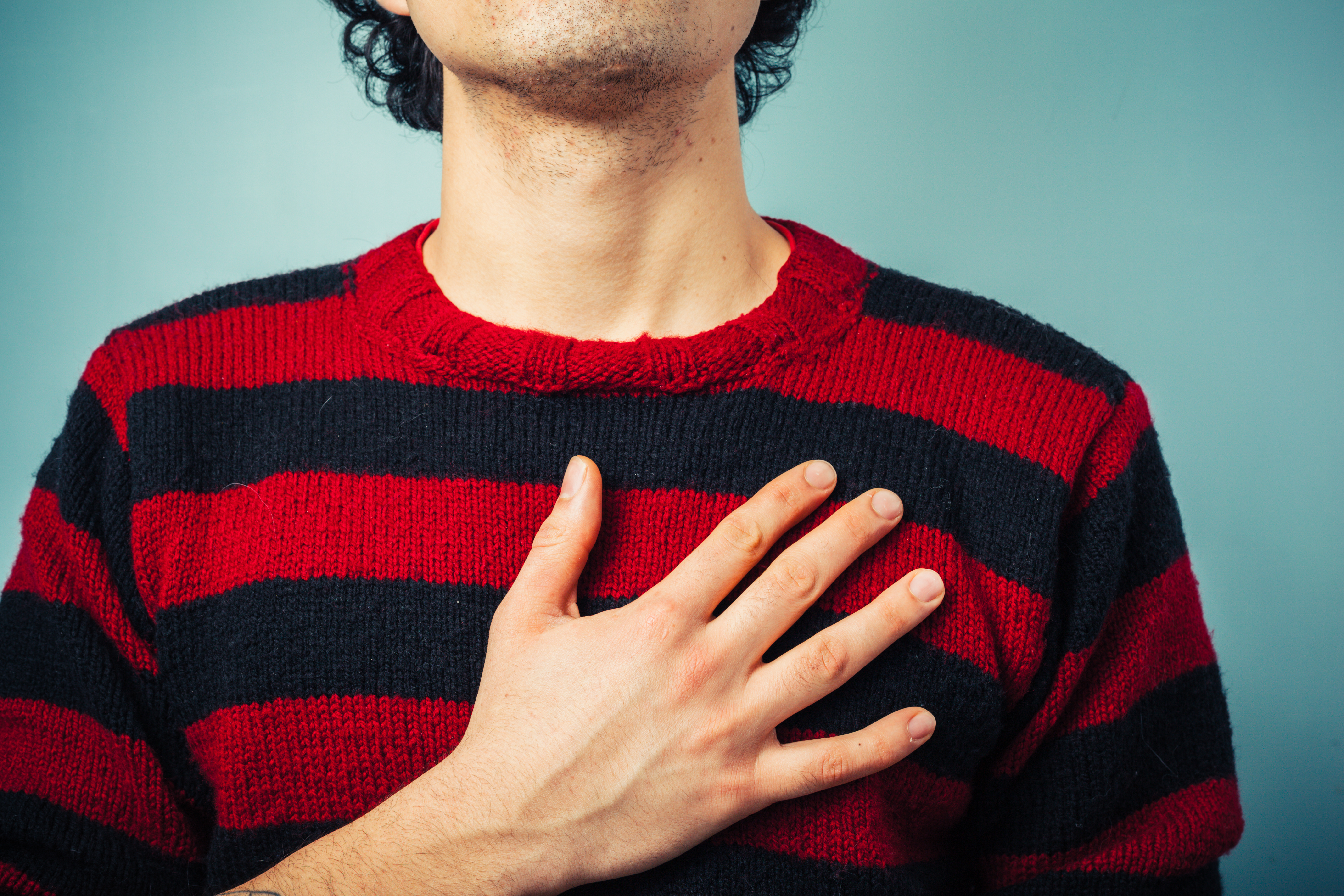 A man places his right hand over his heart to recite the pledge. SHUTTERSTOCK/Lolostock