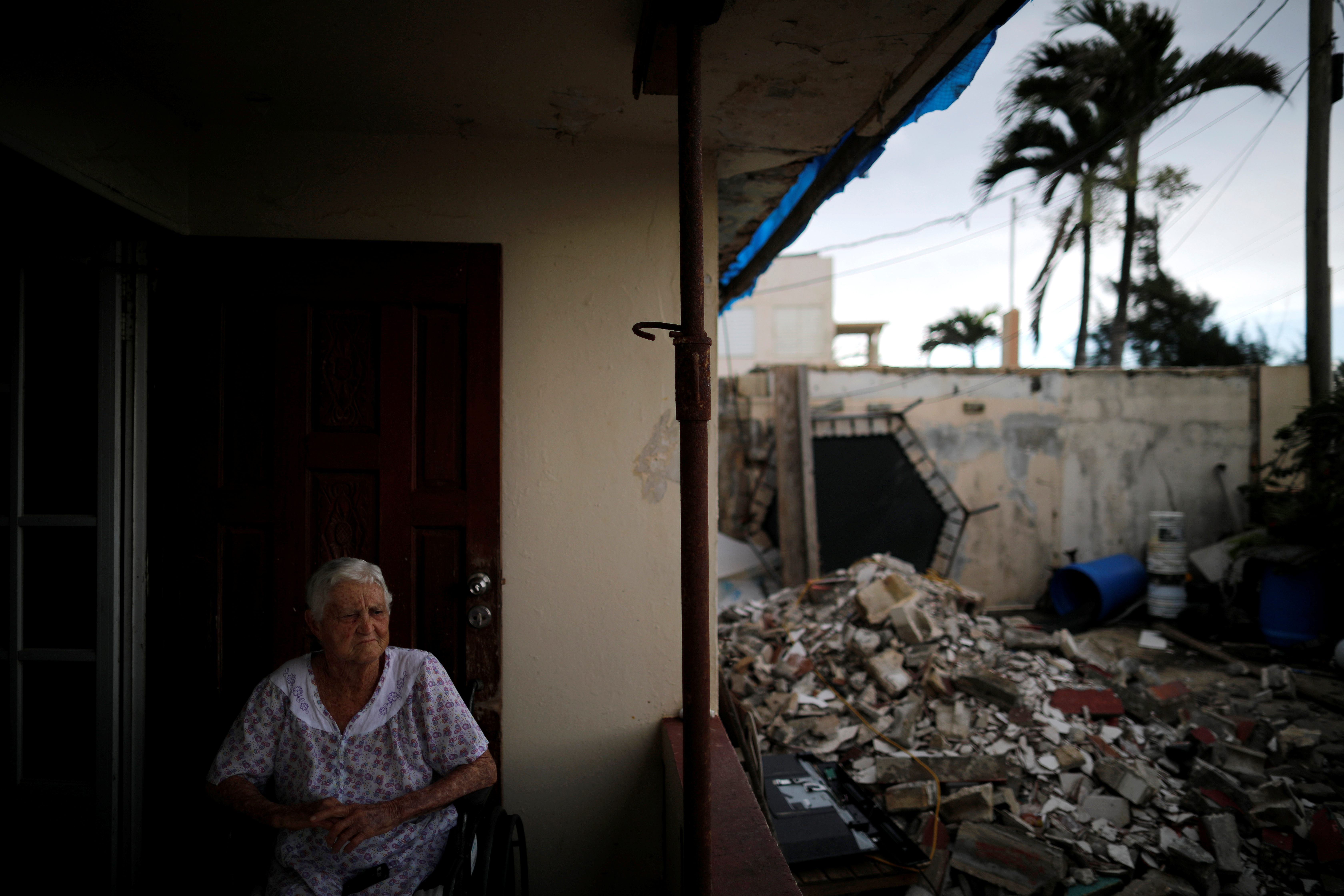 Lucila Cabrera, 86, sits at the porch of her damaged house by Hurricane Maria, a year after the storm devastated Puerto Rico, near Barceloneta, Puerto Rico, September 18, 2018. Picture taken September 18, 2018. REUTERS/Carlos Barria