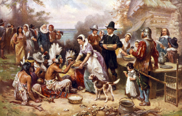 The first Thanksgiving, 1621, Pilgrims and natives gather to share a meal, oil painting by Jean Louis Gerome Ferris, 1932. (Shutterstock/Everett Historical)