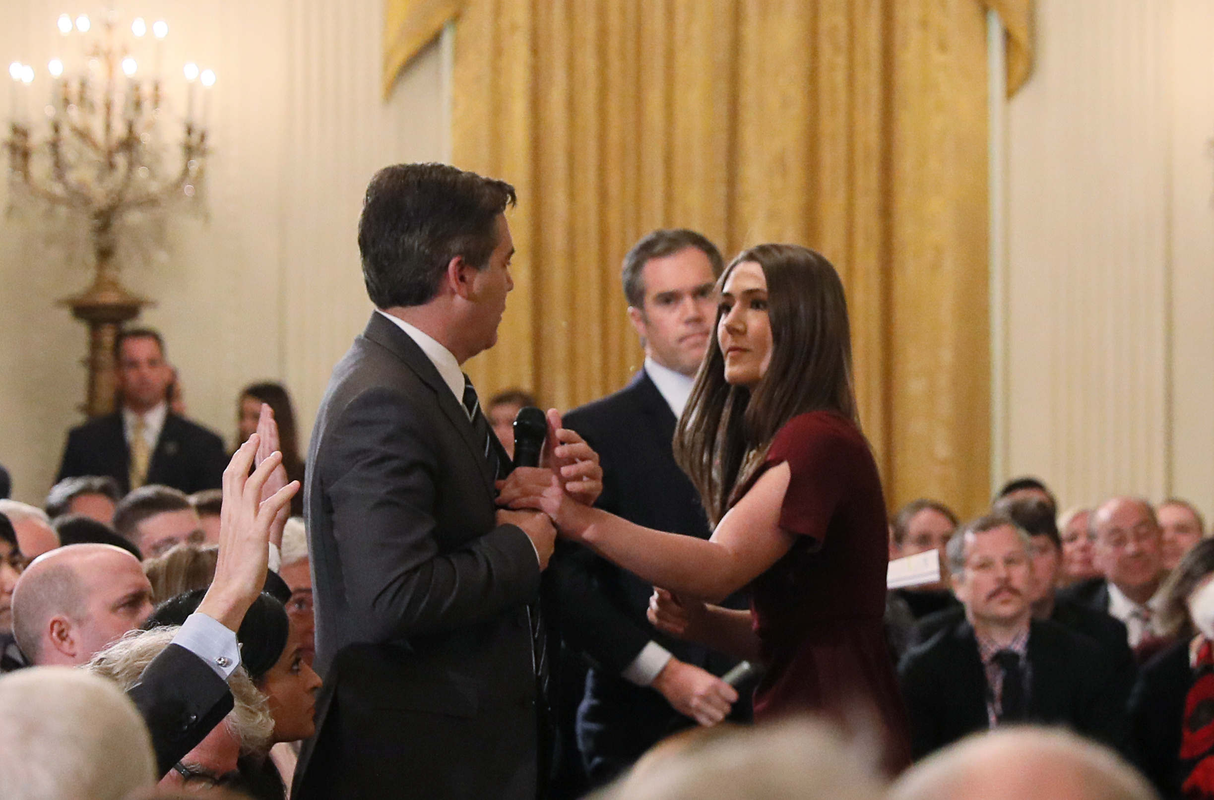 A White House intern reaches for and tries to take away the microphone held by CNN correspondent Jim Acosta as he questions U.S. President Donald Trump during a news conference at the White House in Washington, U.S., November 7, 2018. Picture taken November 7, 2018. REUTERS/Jonathan Ernst (Picture 13 in a sequence of 15) - RC1821E79510