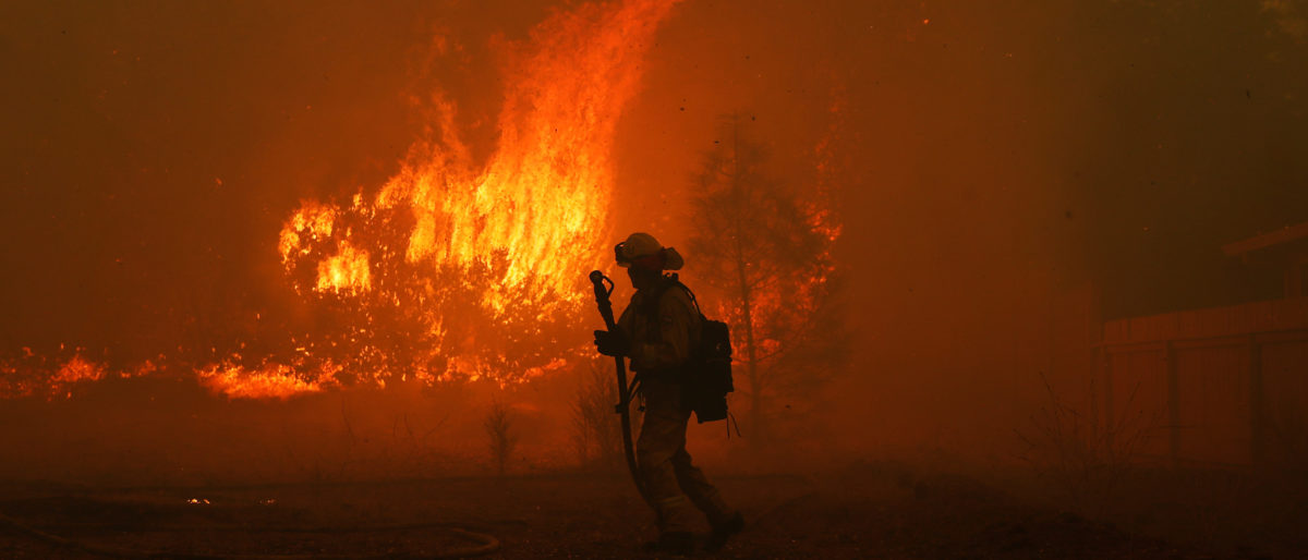 A Cal Fire firefighter monitors a fire near a home while battling the Camp Fire in Paradise, California, U.S. Nov. 8, 2018. REUTERS/Stephen Lam
