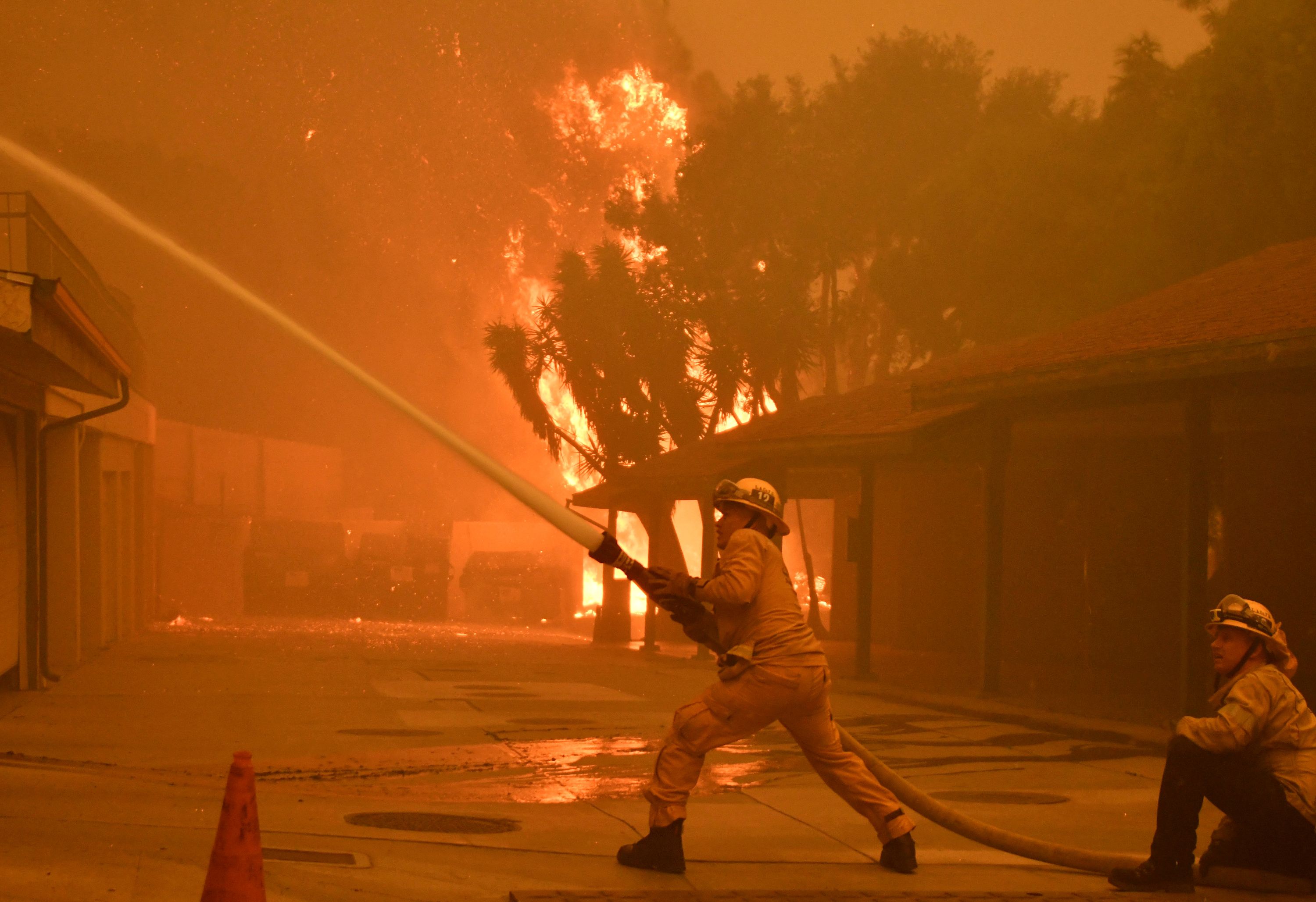 Firefighters hose down a condo unit during the Woolsey Fire in Malibu