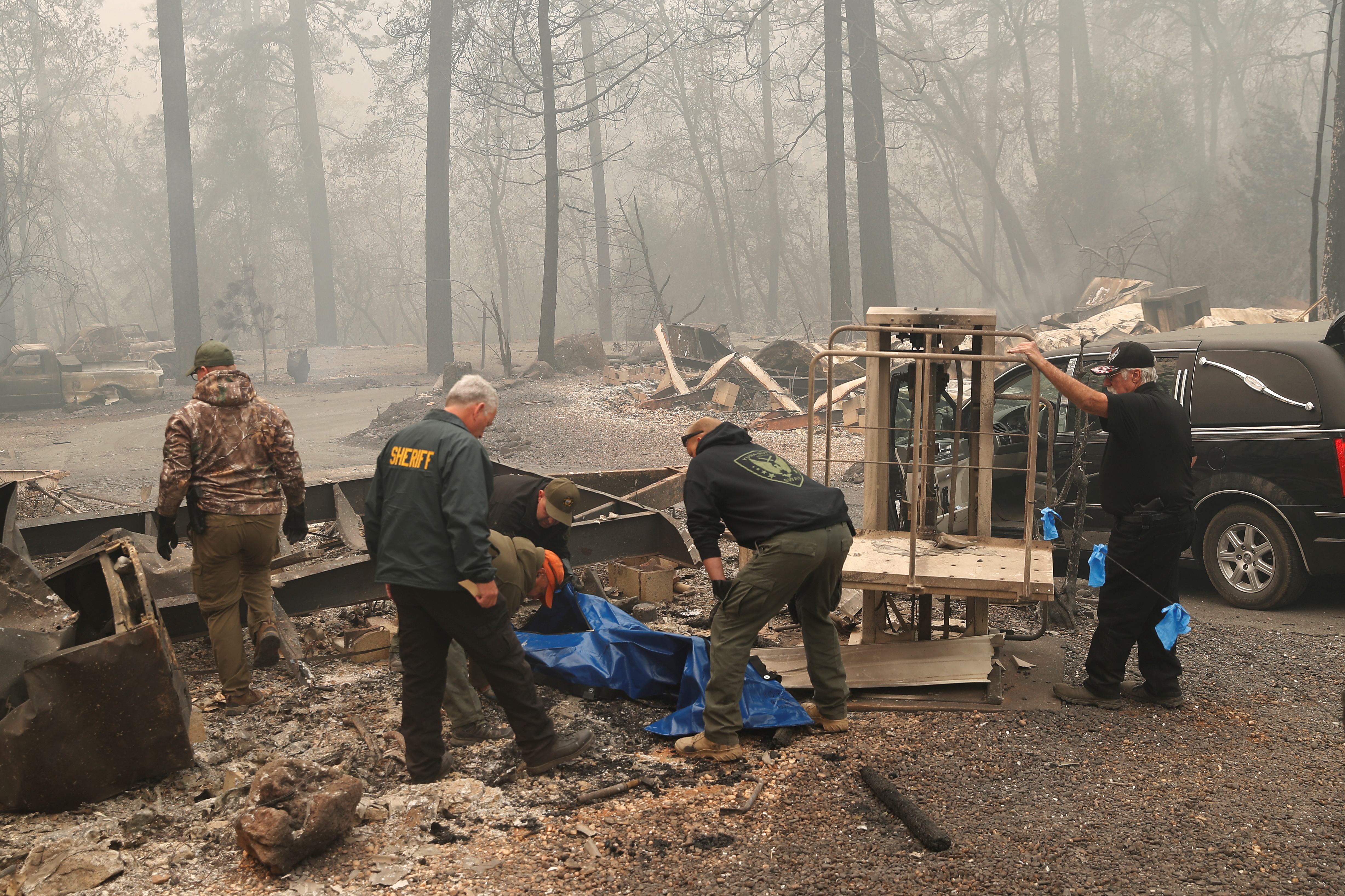 Yuba and Butte County Sheriff deputies carry a body bag with a deceased victim during the Camp fire in Paradise