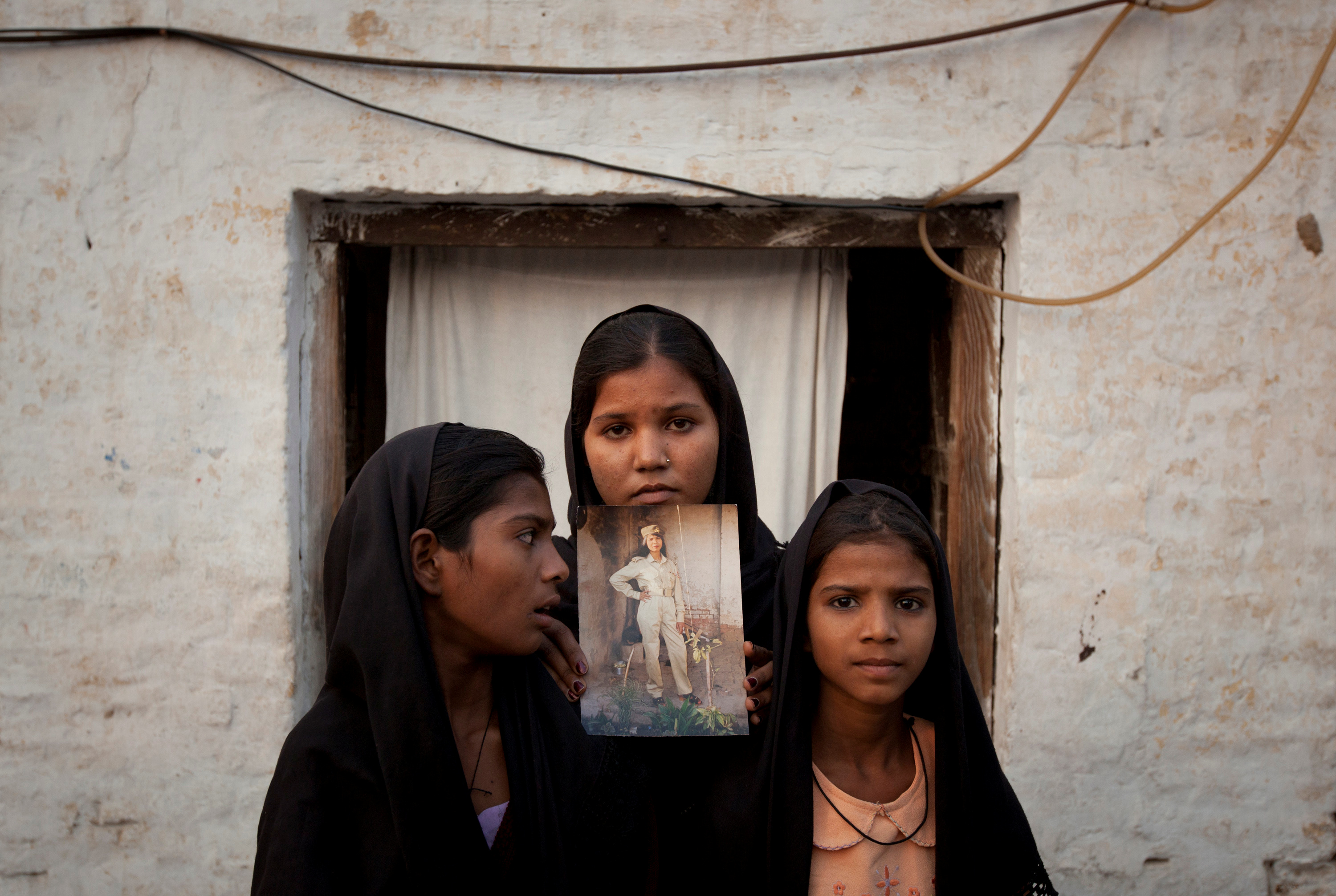 The daughters of Pakistani Christian woman Asia Bibi pose with an image of their mother while standing outside their residence in Sheikhupura located in Pakistan's Punjab Province, November 13, 2010. Standing left to right is Esha, 12, Sidra, 18 and Eshum, 10. REUTERS/Adrees Latif/File Photo