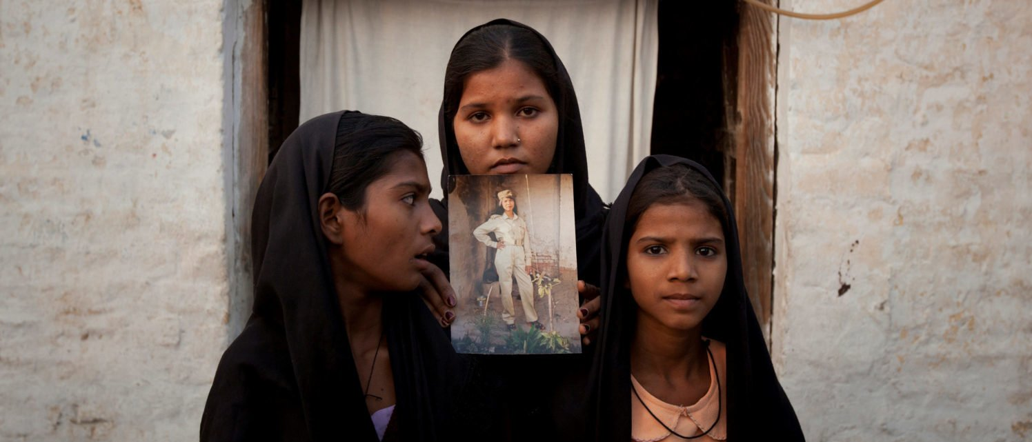 FILE PHOTO: The daughters of Pakistani Christian woman Asia Bibi pose with an image of their mother while standing outside their residence in Sheikhupura located in Pakistan's Punjab Province, November 13, 2010. Standing left to right is Esha, 12, Sidra, 18 and Eshum, 10. REUTERS/Adrees Latif/File Photo