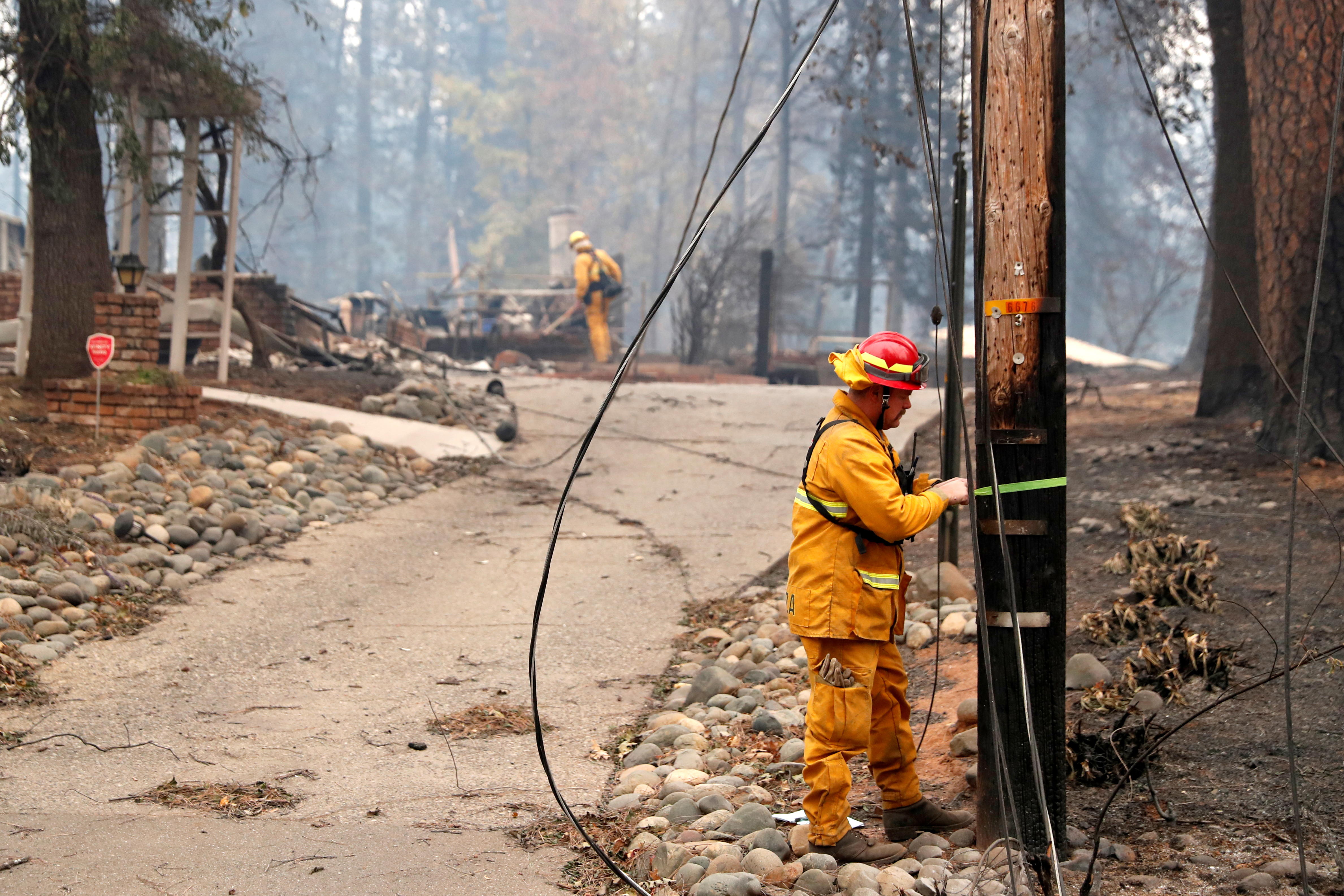 Firefighters inspect a property destroyed by the Camp Fire in Paradise