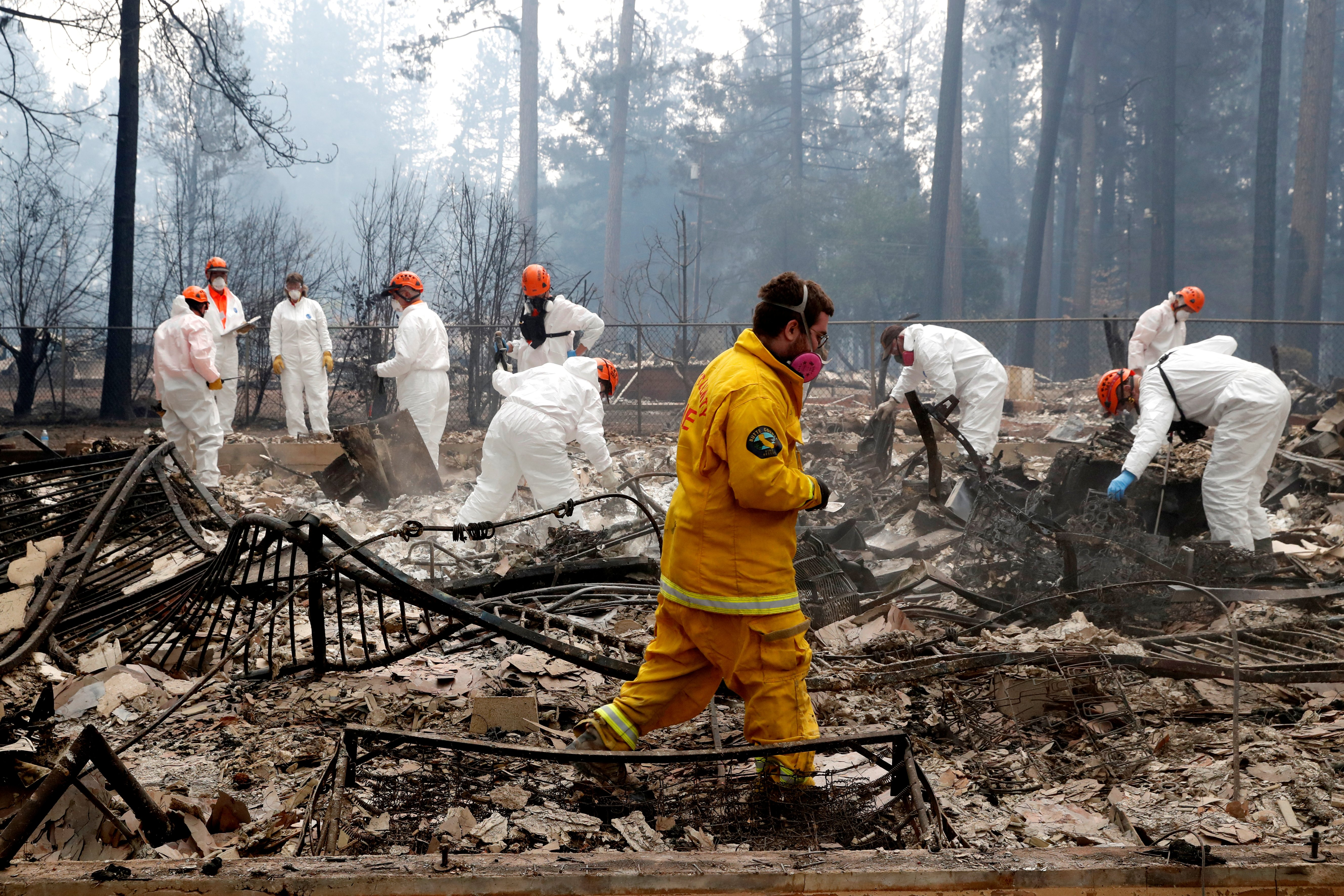 A volunteer search and rescue crew from Calaveras County comb through a home destroyed by the Camp Fire in Paradise