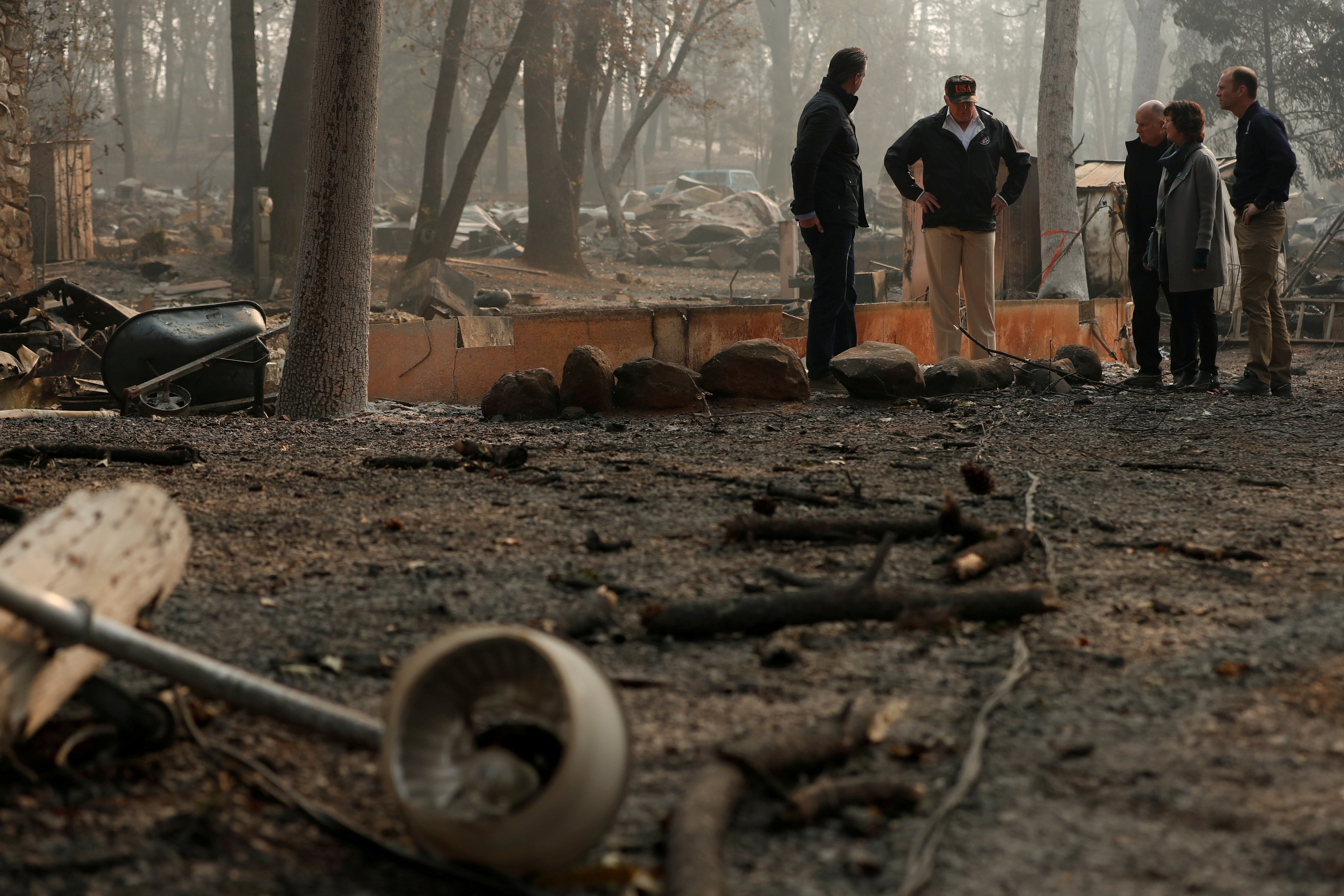 President Donald Trump visits the charred wreckage of Skyway Villa Mobile Home and RV Park with Governor-elect Gavin Newsom Brock Long Paradise Mayor Jody Jones and Governor Jerry Brown in Paradise California