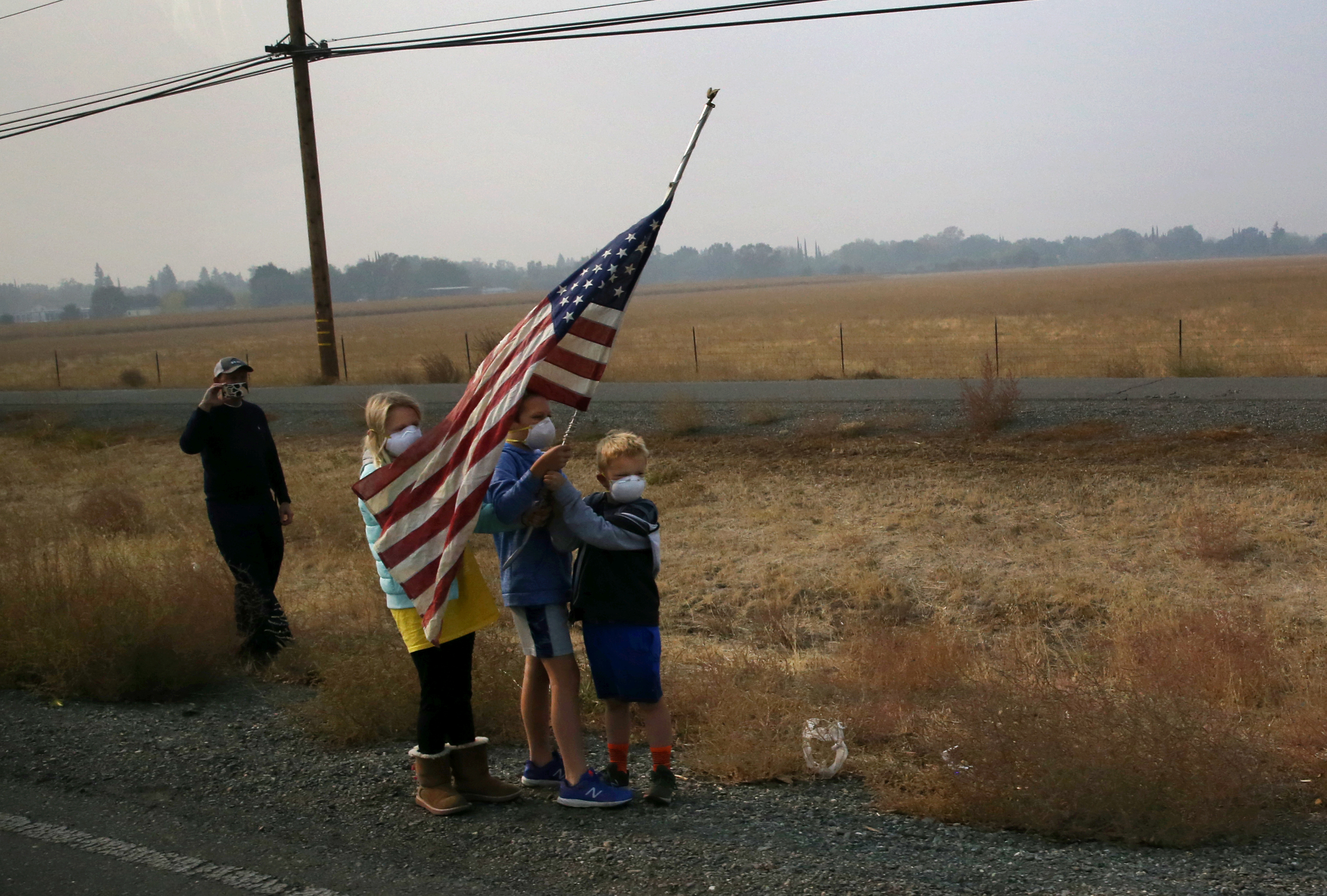 Children hold up an American flag while wearing masks to protect them from smoke in Paradise