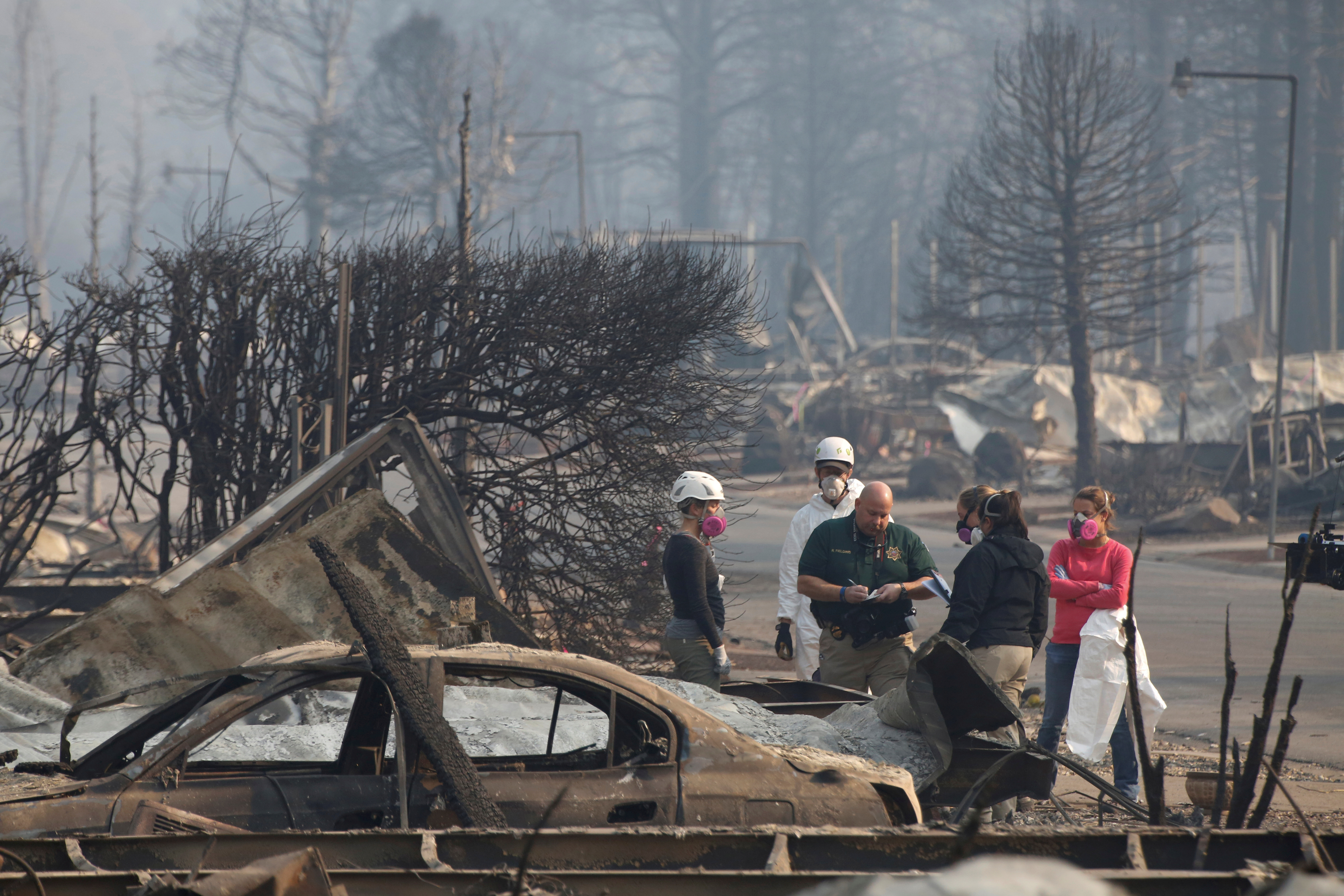 Coroners and forensic anthropologists recover human remains from a trailer home destroyed by the Camp Fire in Paradise