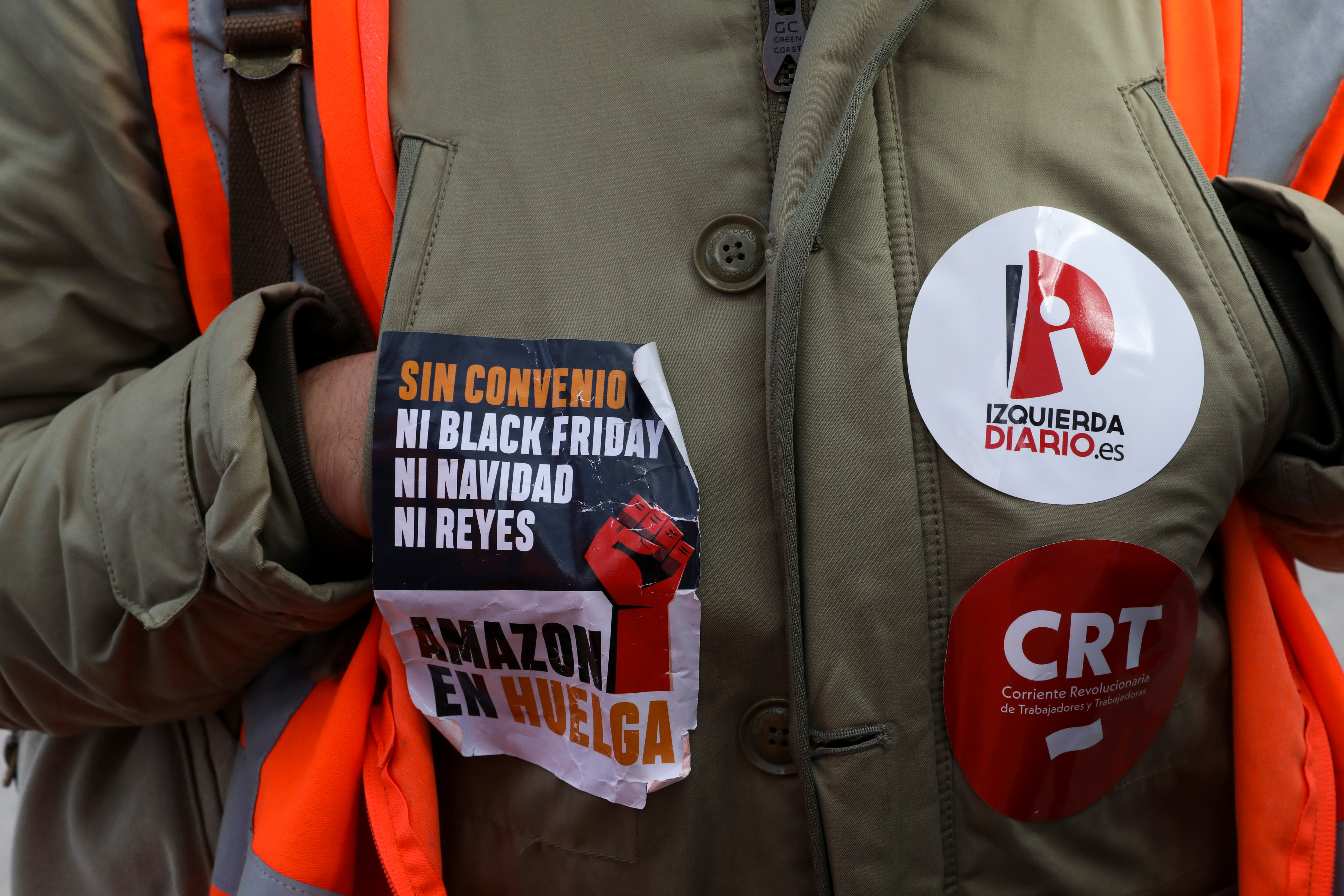 A picket wears stickers related to the strike outside the entrance of an Amazon fulfillment centre in San Fernando de Henares near Madrid, Spain, November 23, 2018. REUTERS/Susana Vera