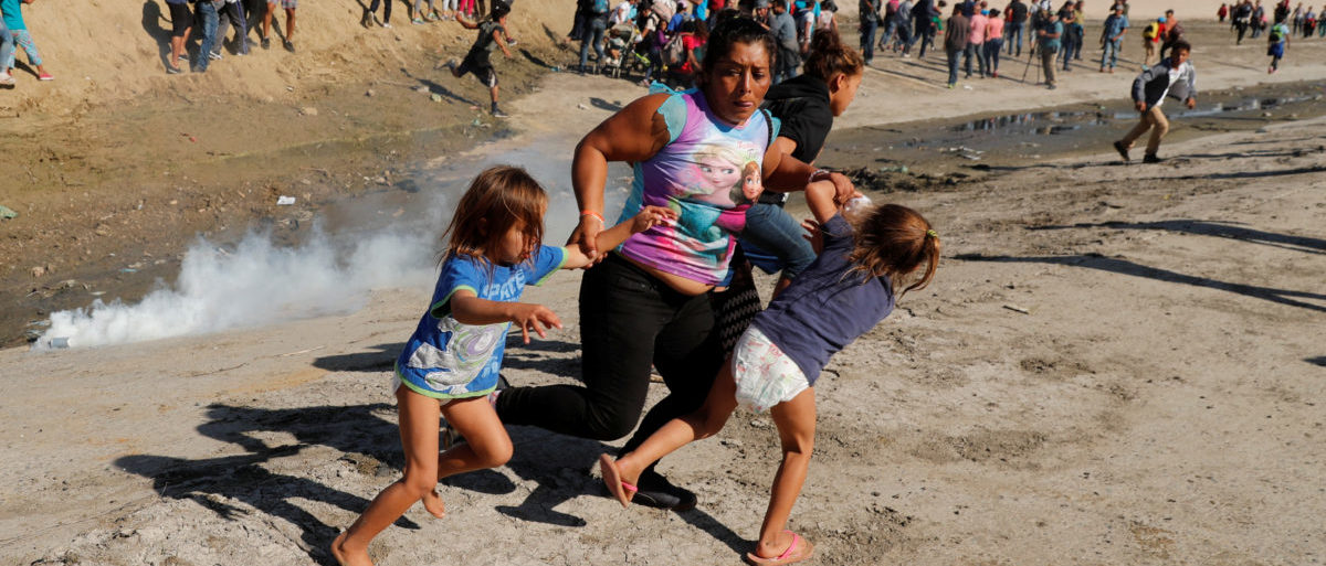A migrant family, part of a caravan of thousands traveling from Central America en route to the United States, run away from tear gas in front of the border wall between the U.S. and Mexico in Tijuana