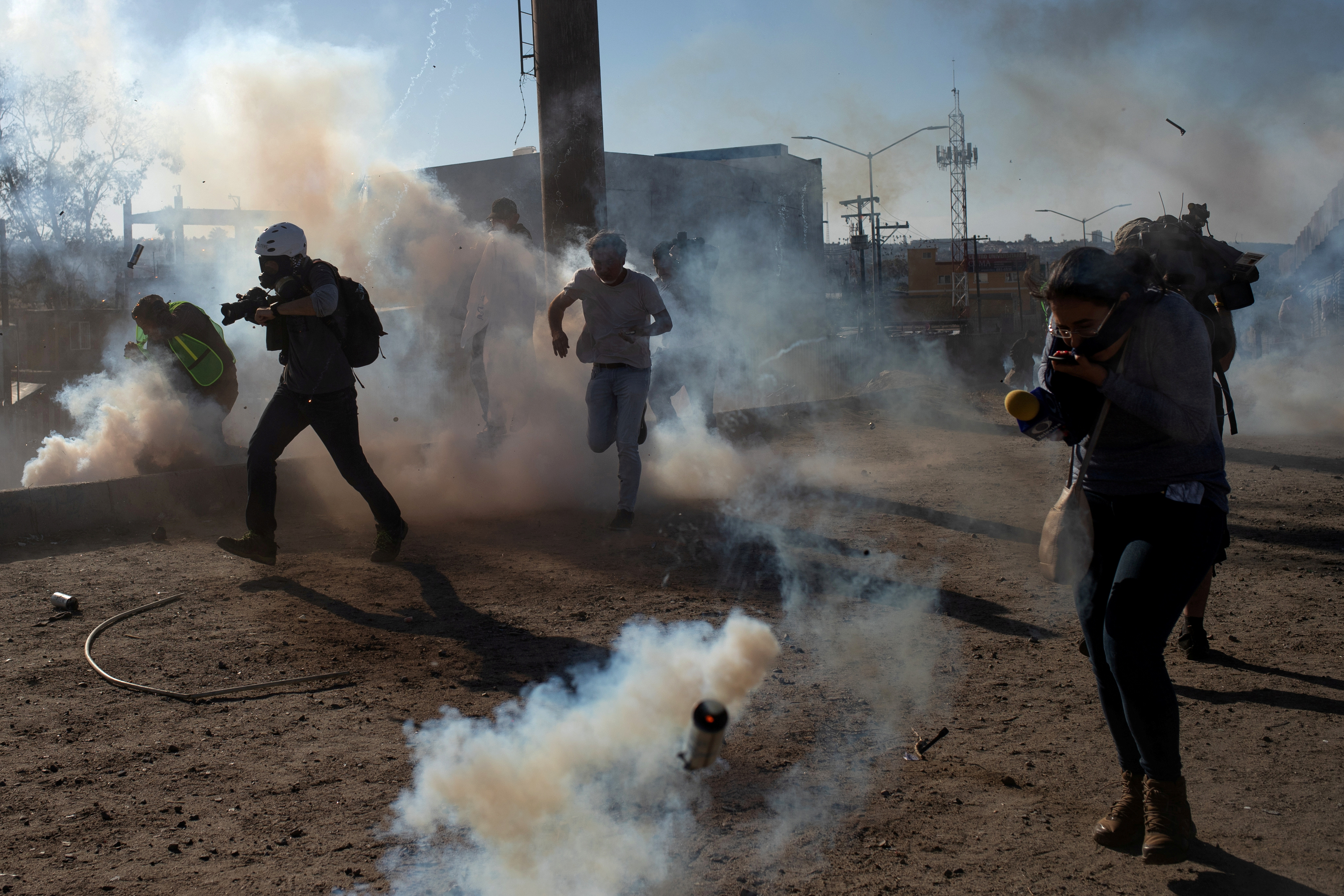 Migrants from Central America and journalists are hit by tear gas after hundreds tried to illegally cross the Mexico border into the U.S. in Tijuana, Mexico