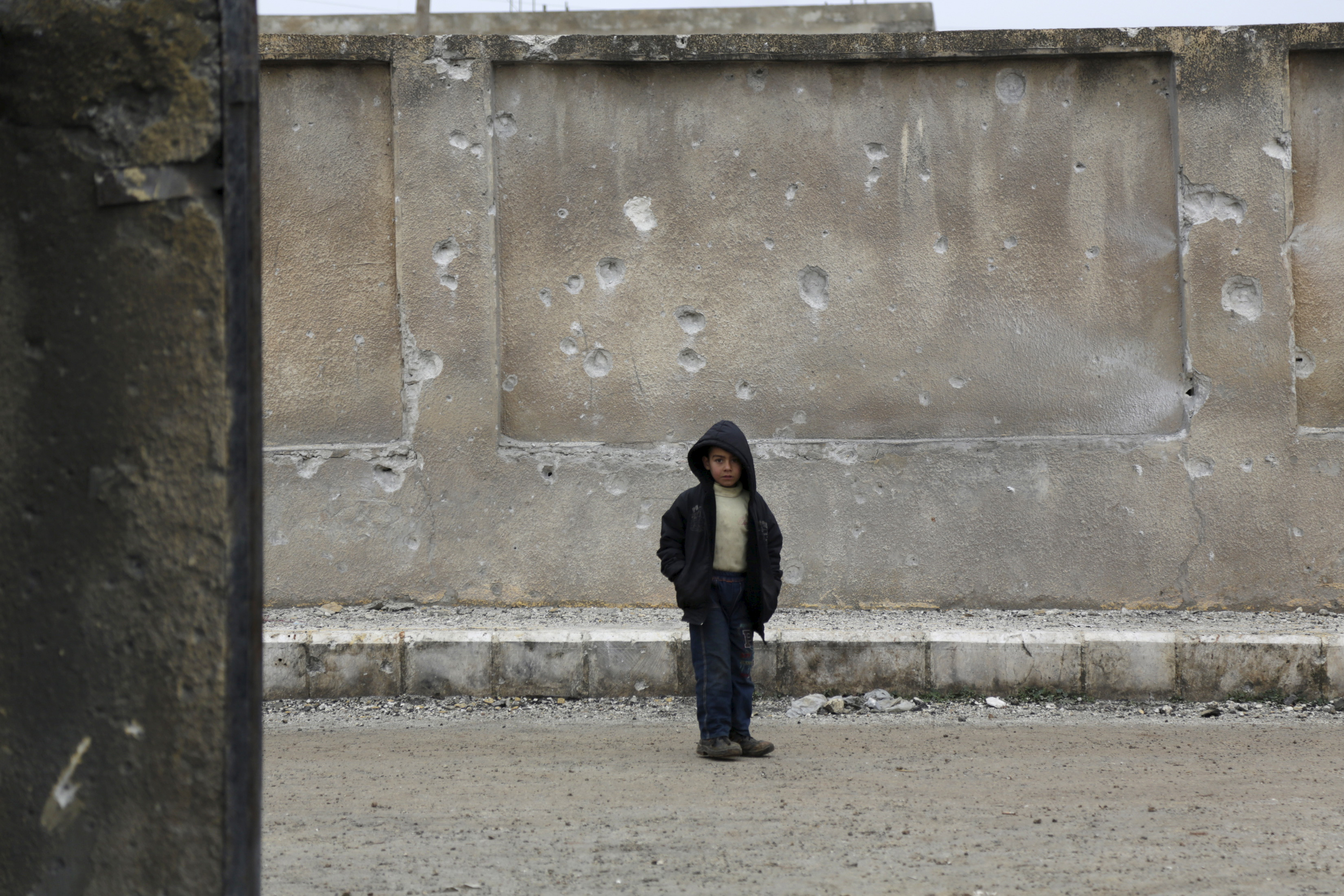 A boy stands near a wall of his school riddled with holes, due to what activists said was an air strike carried out yesterday by the Russian air force in Injara town, Aleppo countryside, Syria January 12, 2016. Bombs dropped by suspected Russian warplanes killed at least 12 Syrian schoolchildren on Monday when they hit a classroom in a rebel-held town in Aleppo province, the Syrian Observatory for Human Rights reported. REUTERS/Khalil Ashawi - GF20000092775