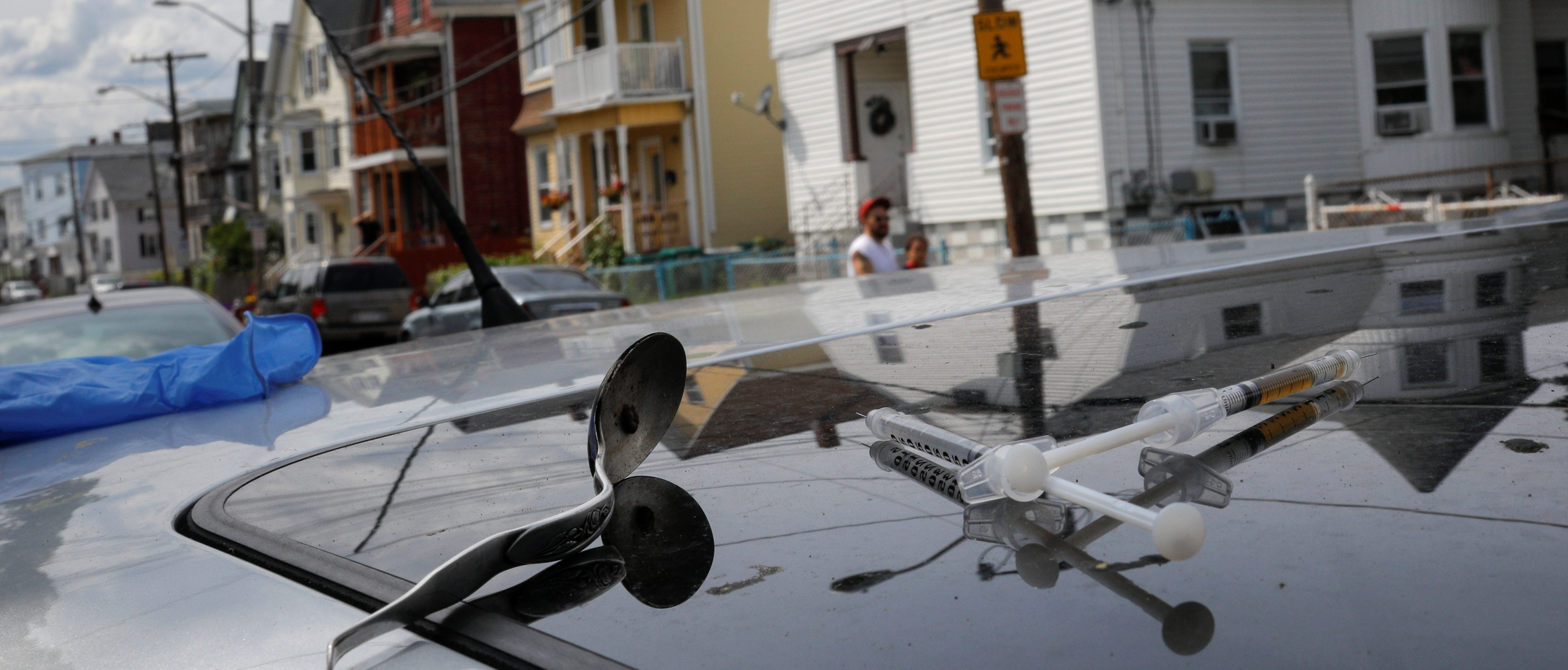 A full syringe, empty syringe and spoon sit on the roof of the car in which a man in his 20's overdosed on an opioid in the Boston suburb of Lynn. REUTERS/Brian Snyder